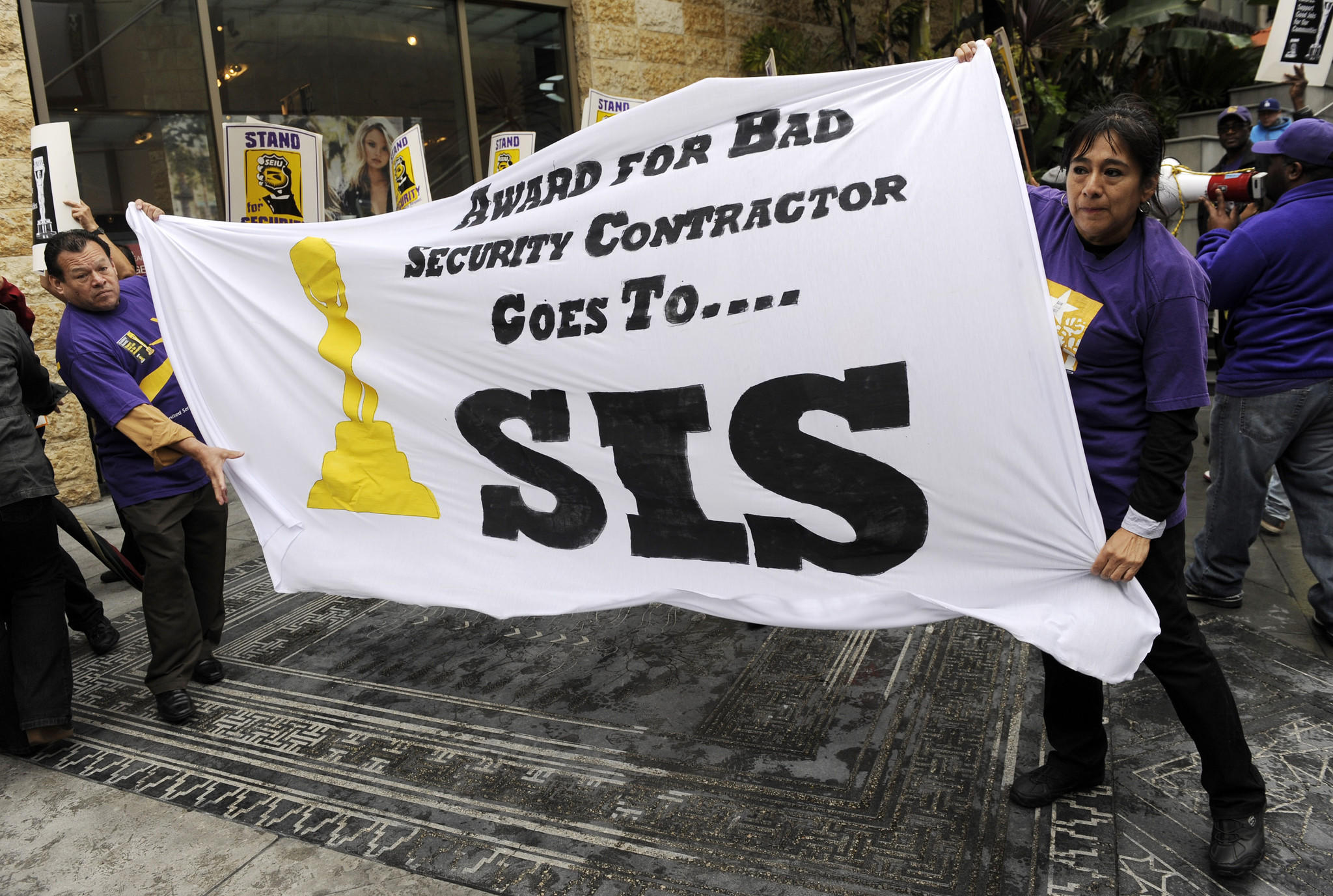 Protesters hold a banner criticizing the Academy of Motion Picture Arts and Sciences' use of the security firm Security Industry Specialists (SIS), in front of the Dolby Theatre, the site of Sunday's 86th Academy Award ceremony, on Friday, Feb. 28 in Los Angeles. Approximately 50 Los Angeles security officers urged the academy to use a unionized security contractor.