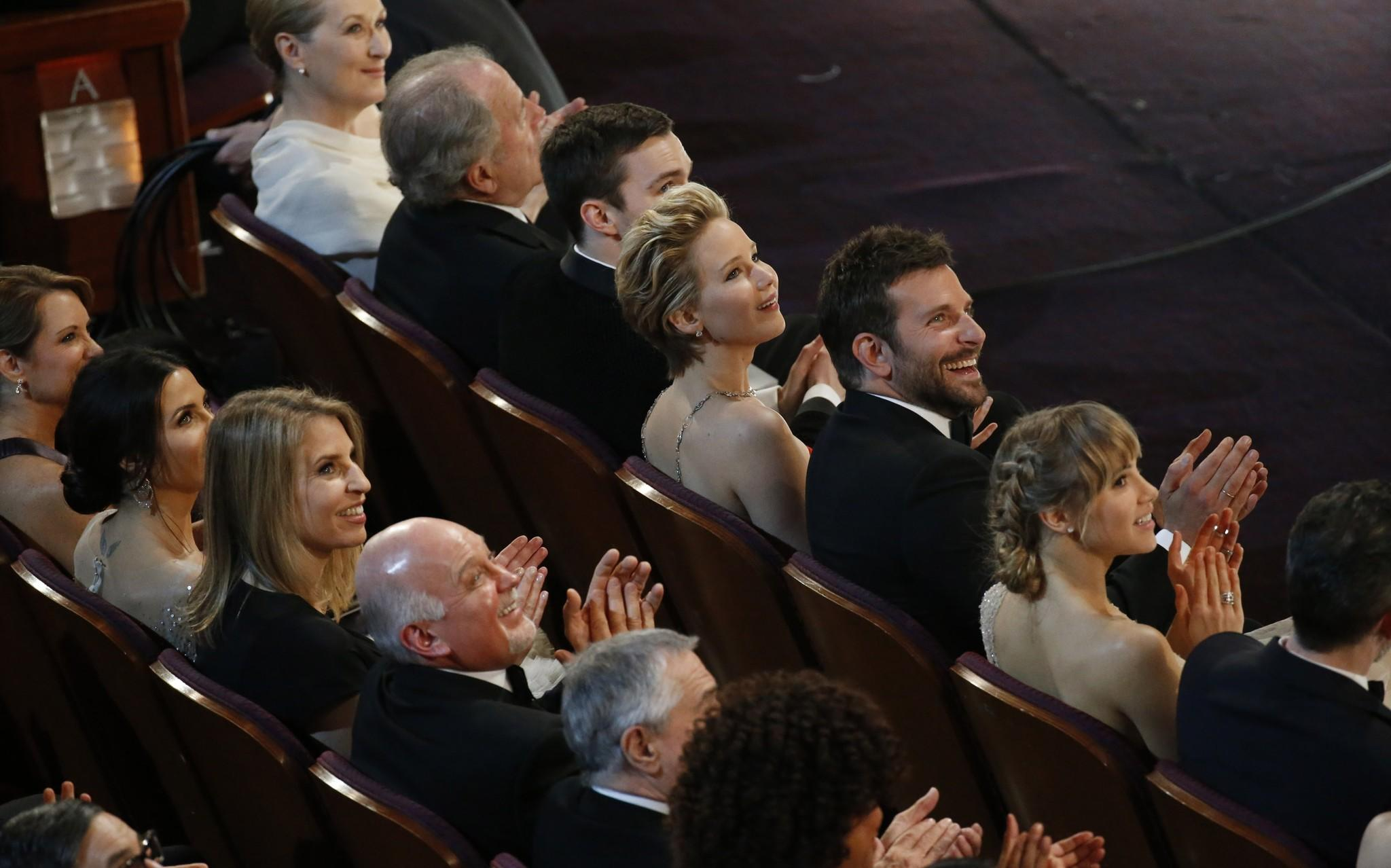 "The cast of ""American Hustle,"" including Jenifer Lawrence and Bradley Cooper, watches on during the telecast of the 86th Academy Awards."