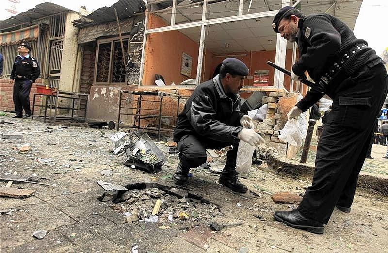 Polic officers collect evidence from the site of a bomb attack at the district court in Islamabad.