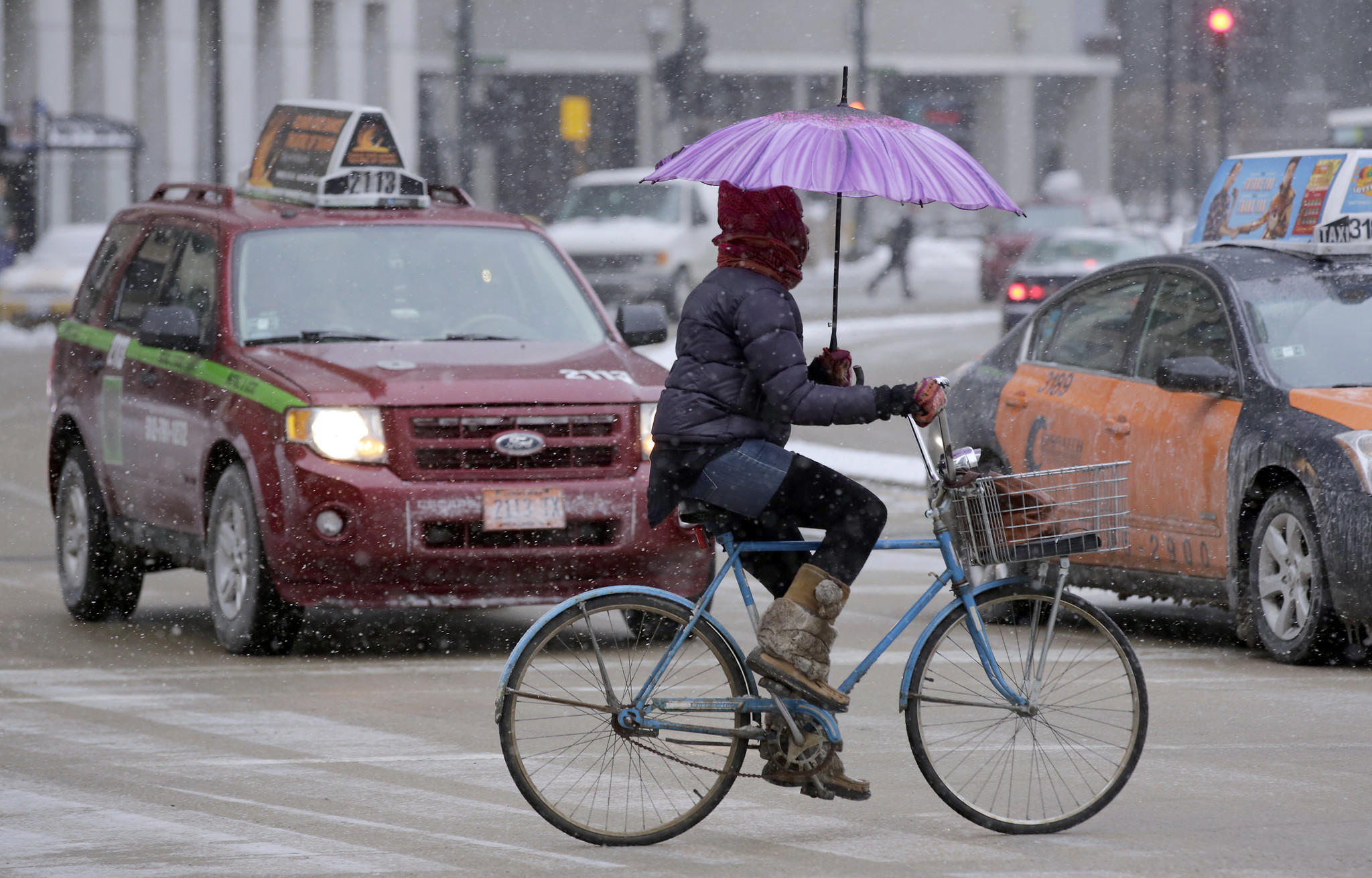 A cyclist displays dexterity and balance as she uses an umbrella against the snow.
