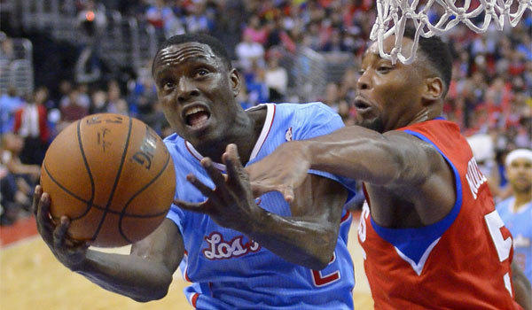 Clippers guard Darren Collison, left, goes up for a shot against Philadelphia forward Arnett Moultrie at Staples Center in downtown Los Angeles.