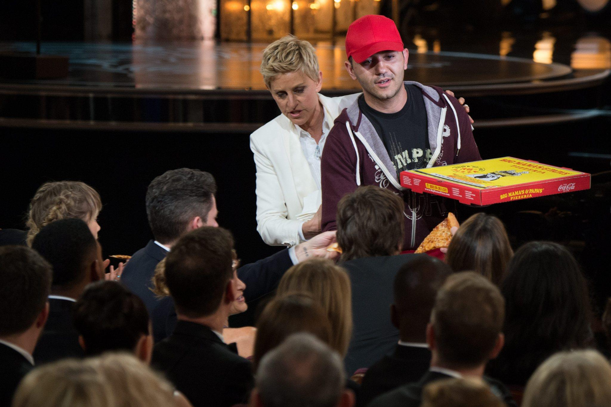 Oscar host Ellen DeGeneres (C) passing out pizza during the 86th annual Academy Awards ceremony.