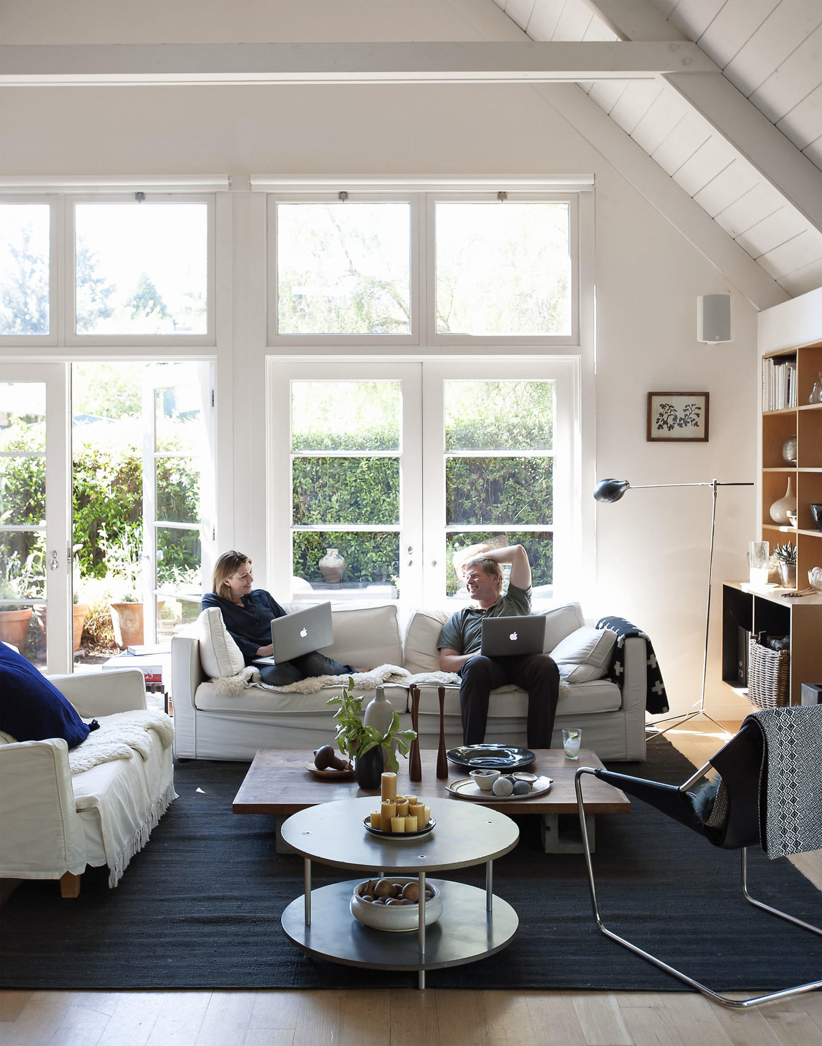 Julie Carlson and husband Josh Groves tend to business on the sofa at their own remodeled home.