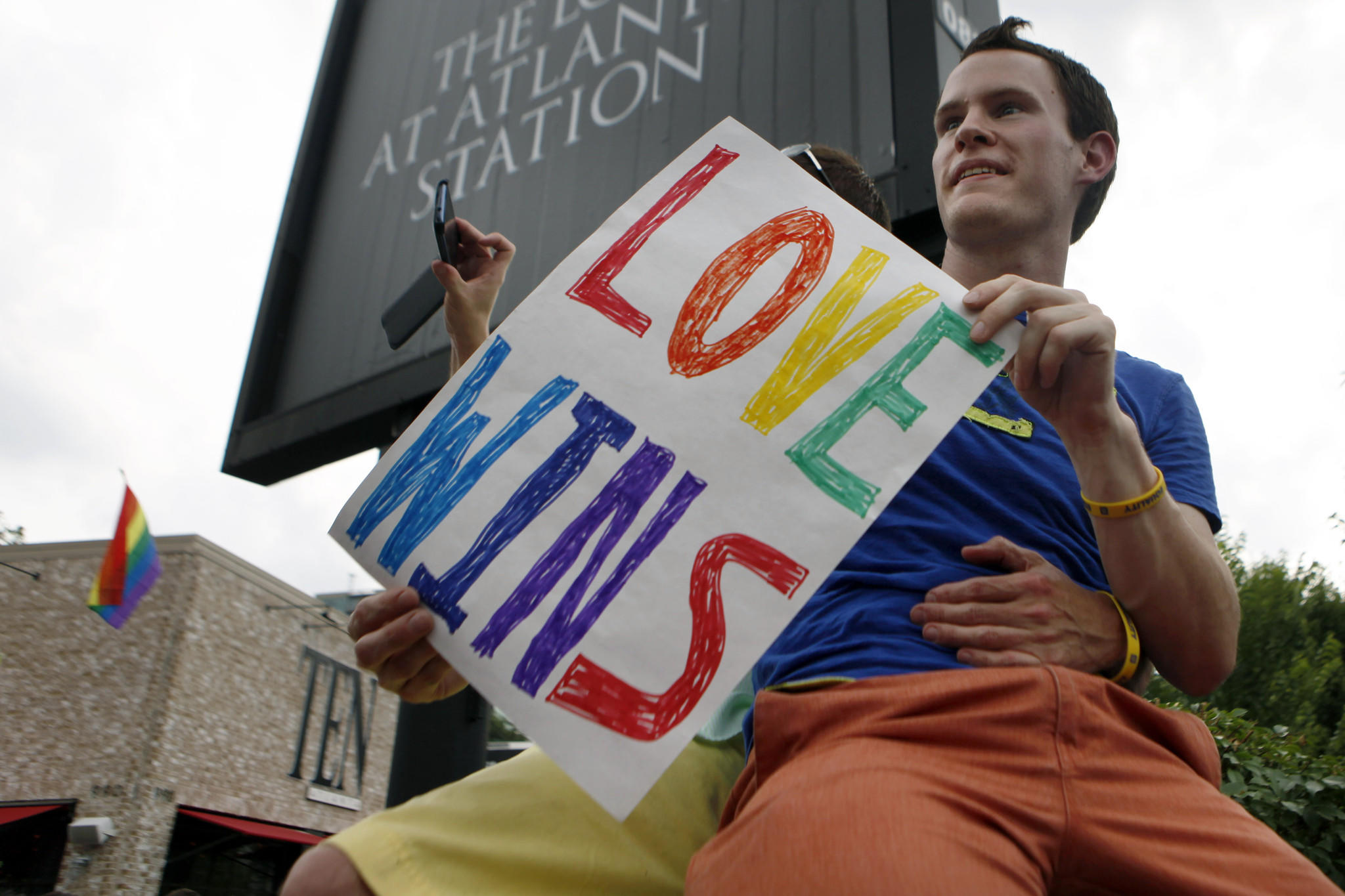 Daniel Hicks sits on a pillar in Atlanta with his boyfriend to watch the local crowd celebrate the U.S. Supreme Court's rulings on two landmark gay rights cases surrounding same-sex marriage.