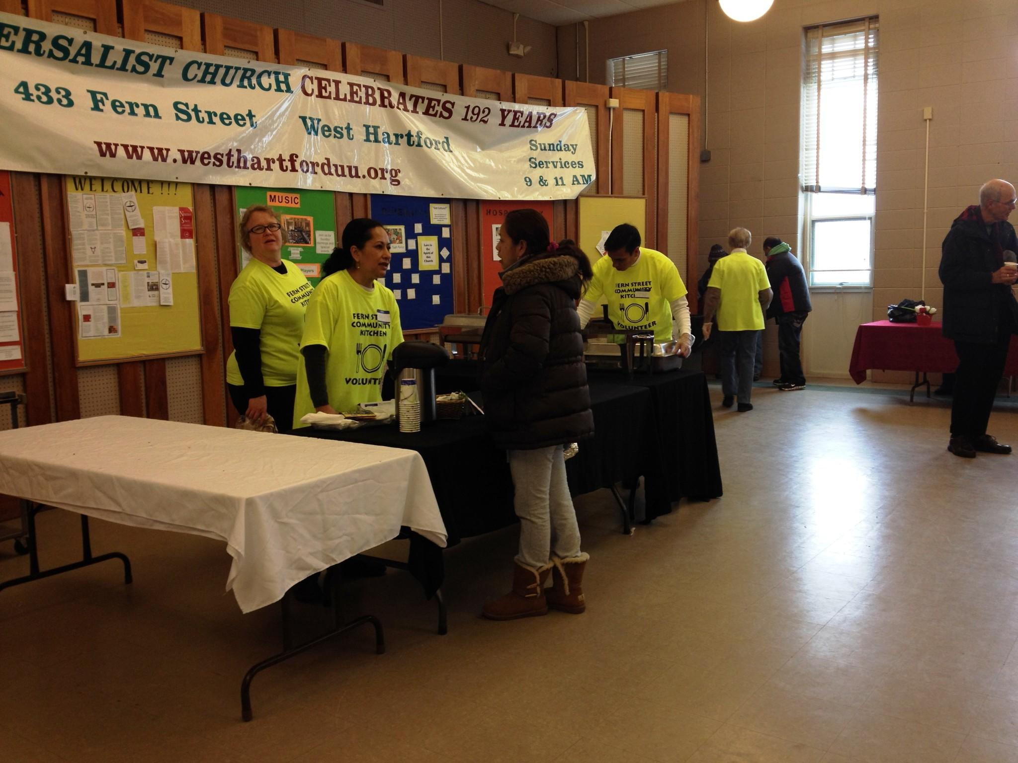 Volunteers clean up and talk to clients at the end of Monday's Fern Street Community Kitchen breakfast at the Universalist Church.