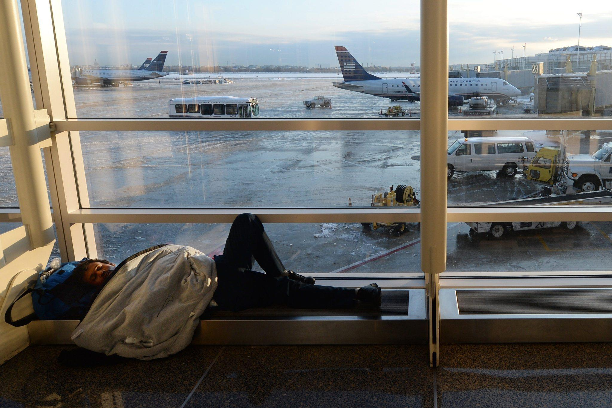 A man tries to sleep by a window at Ronald Reagan Washington National Airport in Arlington, Va. Airline delays and cancellations have cost passengers and carriers $5.8 billion this winter, a study has found.