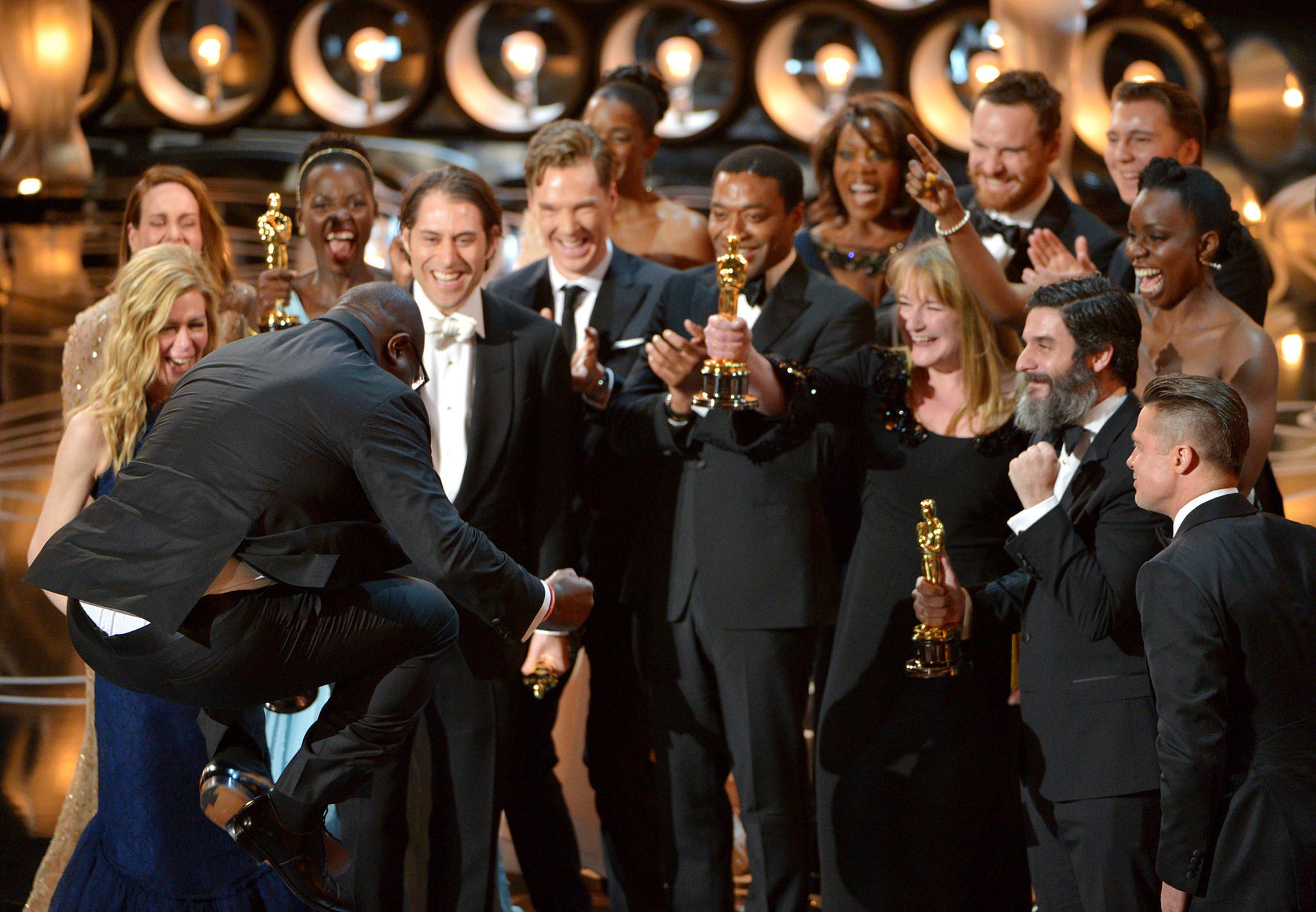 """Director Steve McQueen jumps for joy as he and cast and crew members of """"12 Years a Slave"""" accept the award for best picture during the Oscars on Sunday."""