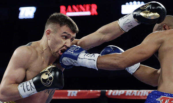 Vasyl Lomachenko, left, throws a left jab as he takes a punch from by Orlando Salido in their featherweight fight on Saturday. Lomachenko lost in a split decision.