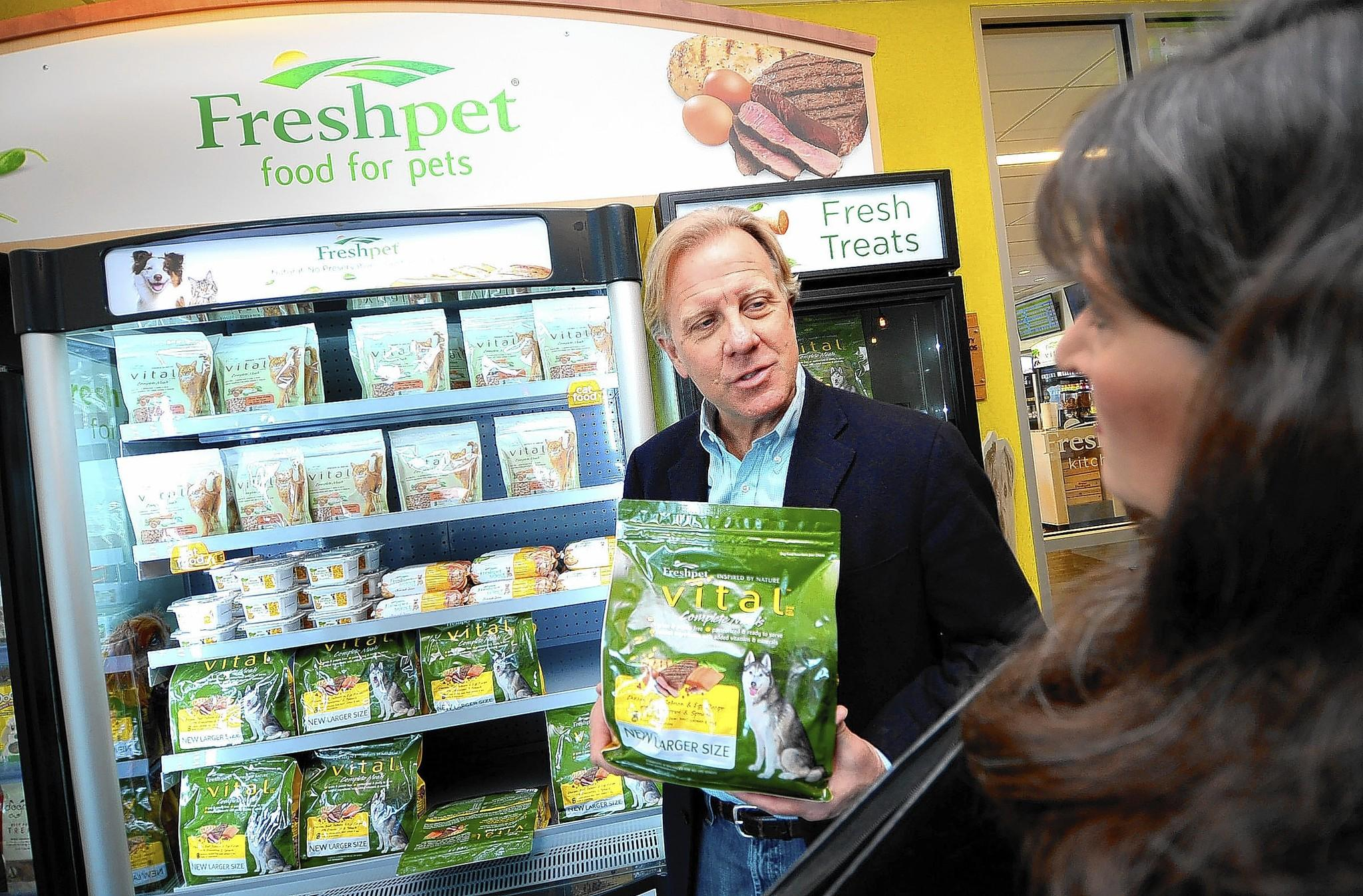 Freshpet CEO Richard Thompson talks with plant visitor Cindy Zimmerman of Clark's Summit. Behind him is one of Freshpet's standard display case/refrigerators often seen in stores where the product is sold. The Freshpet natural pet food company is expanding its $25 million facility.