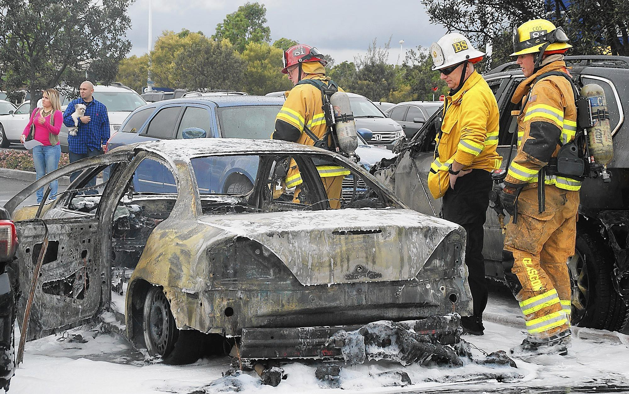After extinguishing the blaze, Costa Mesa firefighters examine the remains of a car that caught on fire Sunday afternoon in Ikea's parking lot.