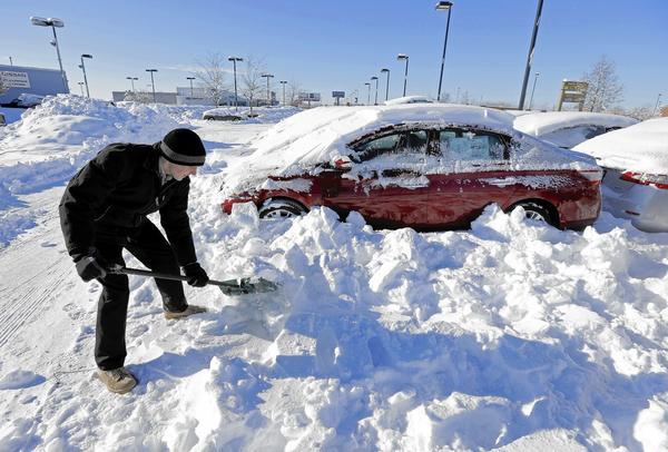 After falling 3% in January, auto sales were unchanged at about 1.2 million vehicles in February, unchanged from the same month a year earlier, according to Autodata Corp. Above, a salesmen digs out cars covered in snow at a dealership in Indianapolis.