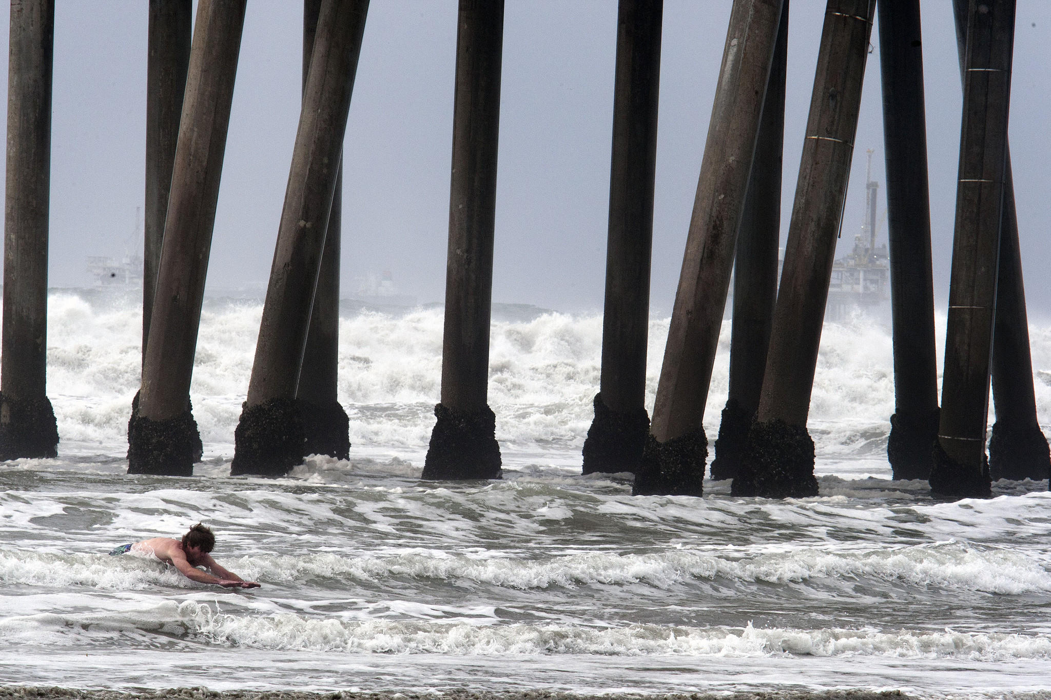 A man swims in the surf Saturday at Huntington Beach. A new study suggests a three-day waiting period after rainfall is not long enough to protect ocean swimmers and surfers from pathogens swept into the water.