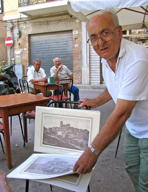 A merchant offers souvenir pictures in the Piazza Liberta in Salemi.