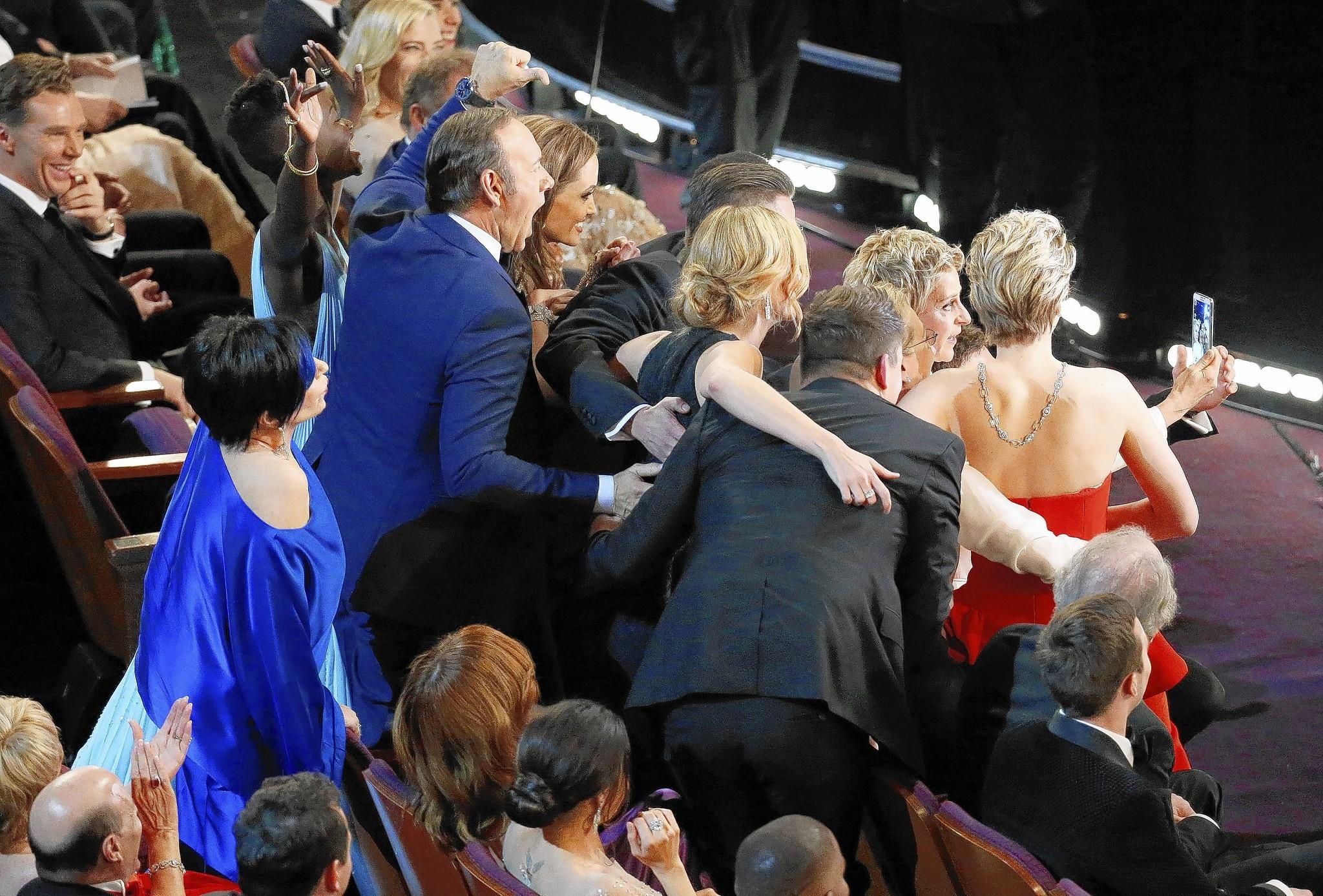 As she hosts the Academy Awards, Ellen DeGeneres gets a photo of herself and several other stars, using a Samsung smartphone.