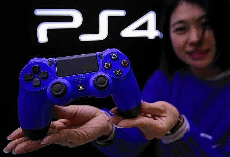 Staff at the PlayStation 4 launch event poses with PlayStation 4's game controller before its domestic launch event at the Sony Showroom in Tokyo.