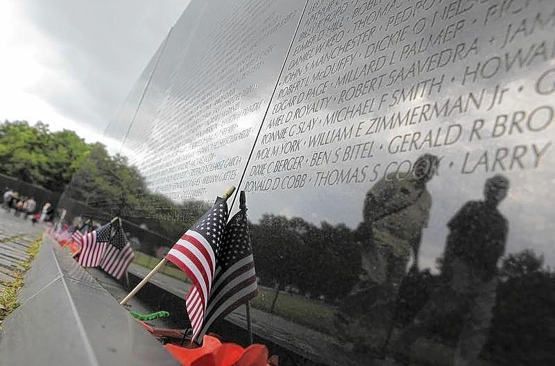 Visitors are reflected in the Vietnam Veterans Memorial wall.