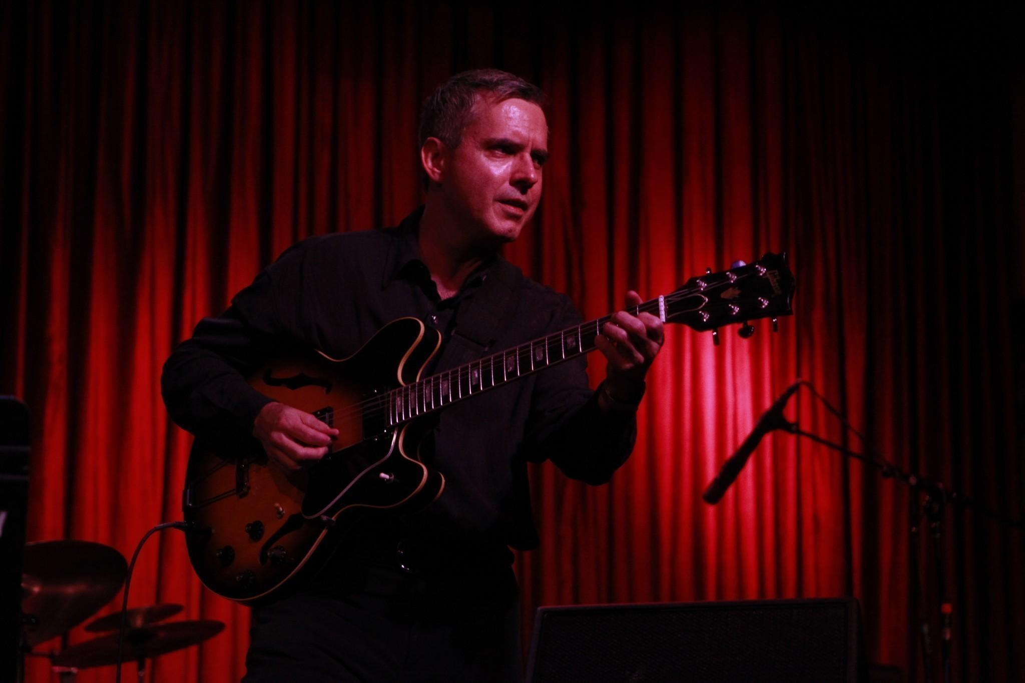 Father John Moulder playing the guitar during a show with the Alejo Poreda and Friends at Jazz Showcase in Chicago.