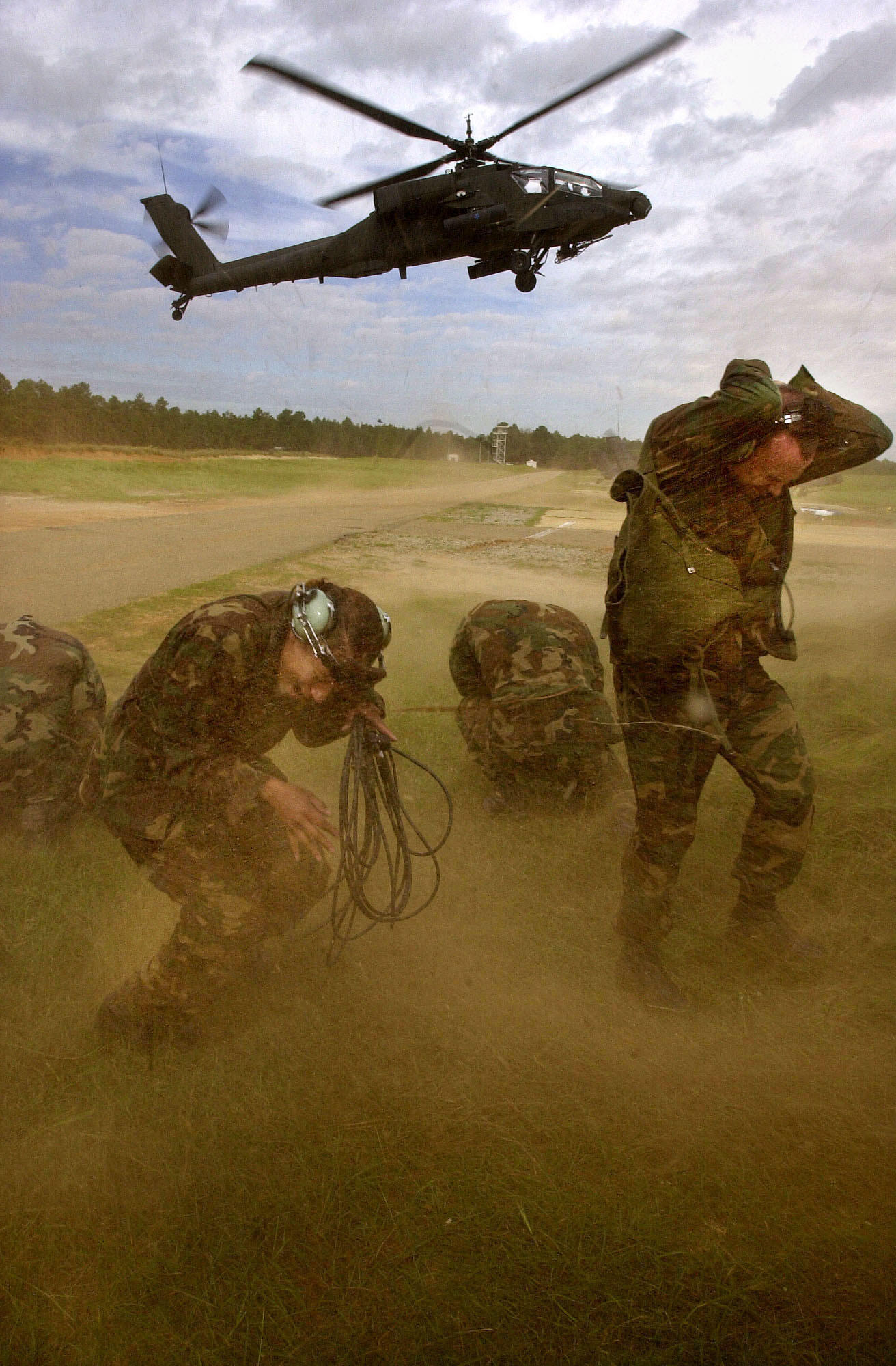 Members of the First Battalion 229th Aviation Regiment, 18th Airborn Corps cover their heads as an AH-64 Apache Helicopter takes off at Fort Bragg Military Post in North Carolina on Tuesday, Sept. 25, 2001. (Heather Stone/Chicago Tribune) (Fort Bragg, North Carolina, Army Base, Military Training, Maneuvers, Terrorism, Terrorist Attacks, 82nd Airborne Division Speical Operations Force, Helicopter)