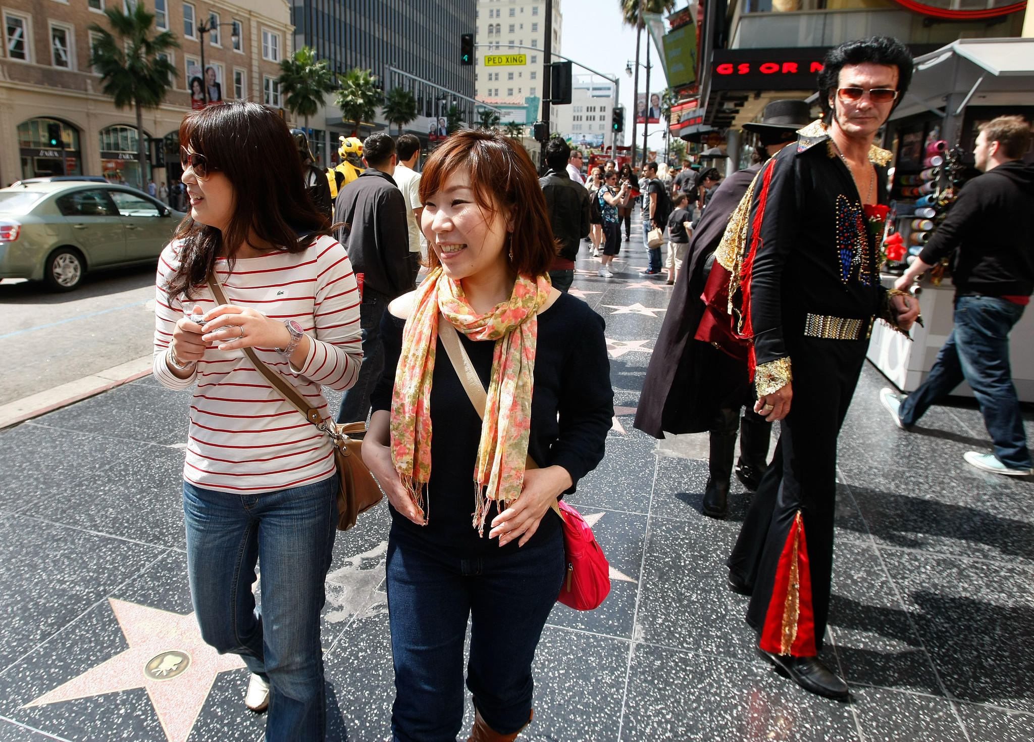 Tourists Miwako Tsugawa, left, and Yuka Watanabe, from Nagoya, Japan, check out the sights while walking along Hollywood Boulevard.