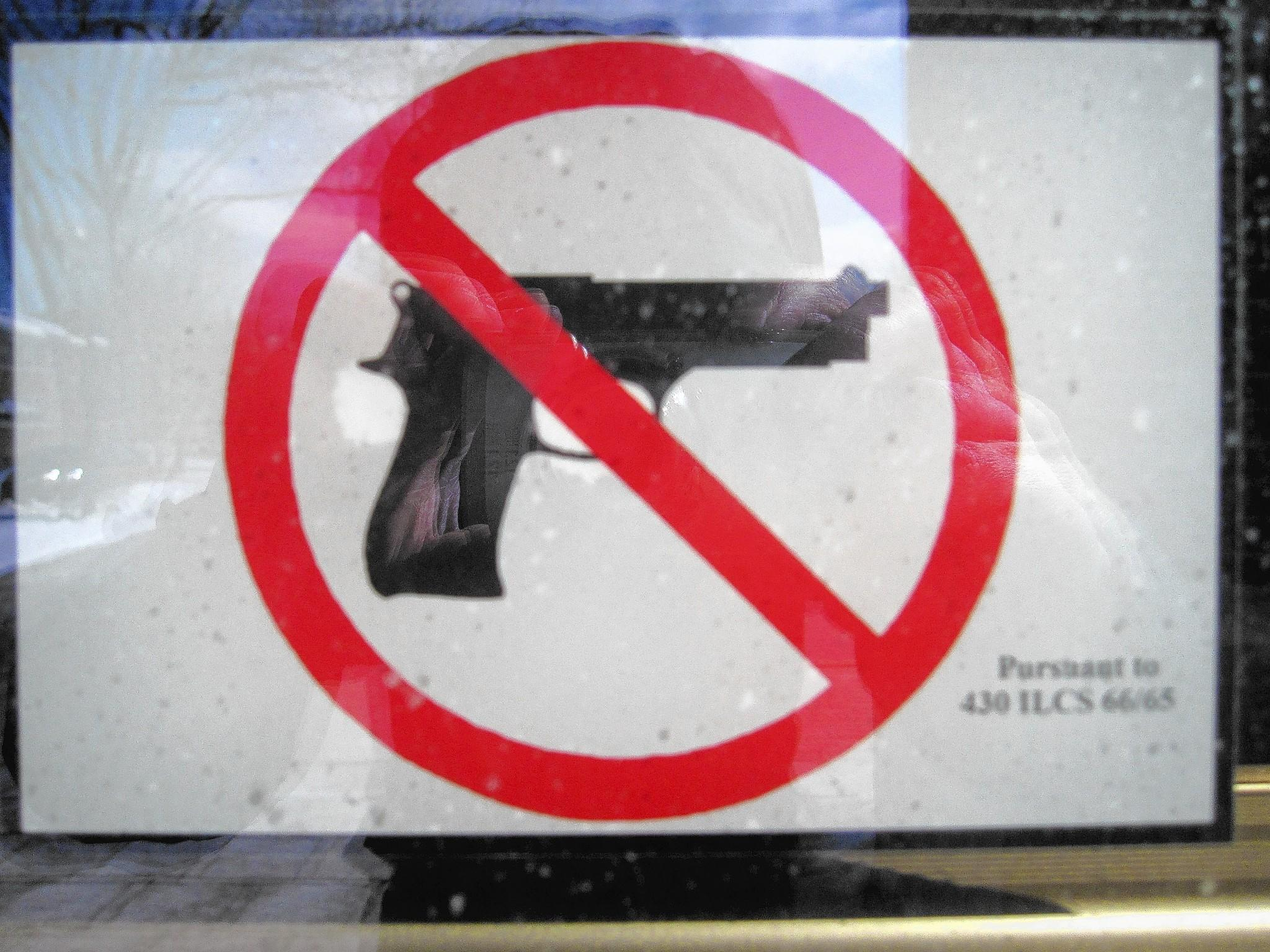 A sign bans guns at the La Grange Public Library, one of the places concealed weapons are forbidden under a new state law.