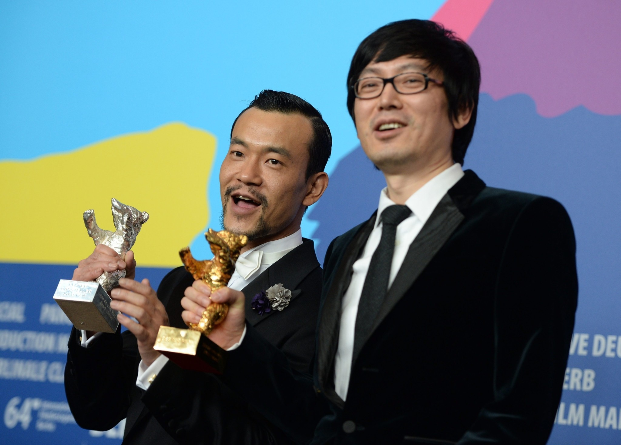 """""""Black Coal, Thin Ice"""" star Fan Liao, left, holds the Silver Bear for best actor, and director Yinan Diao has the Golden Bear award for best film at the Berlin Film Festival."""