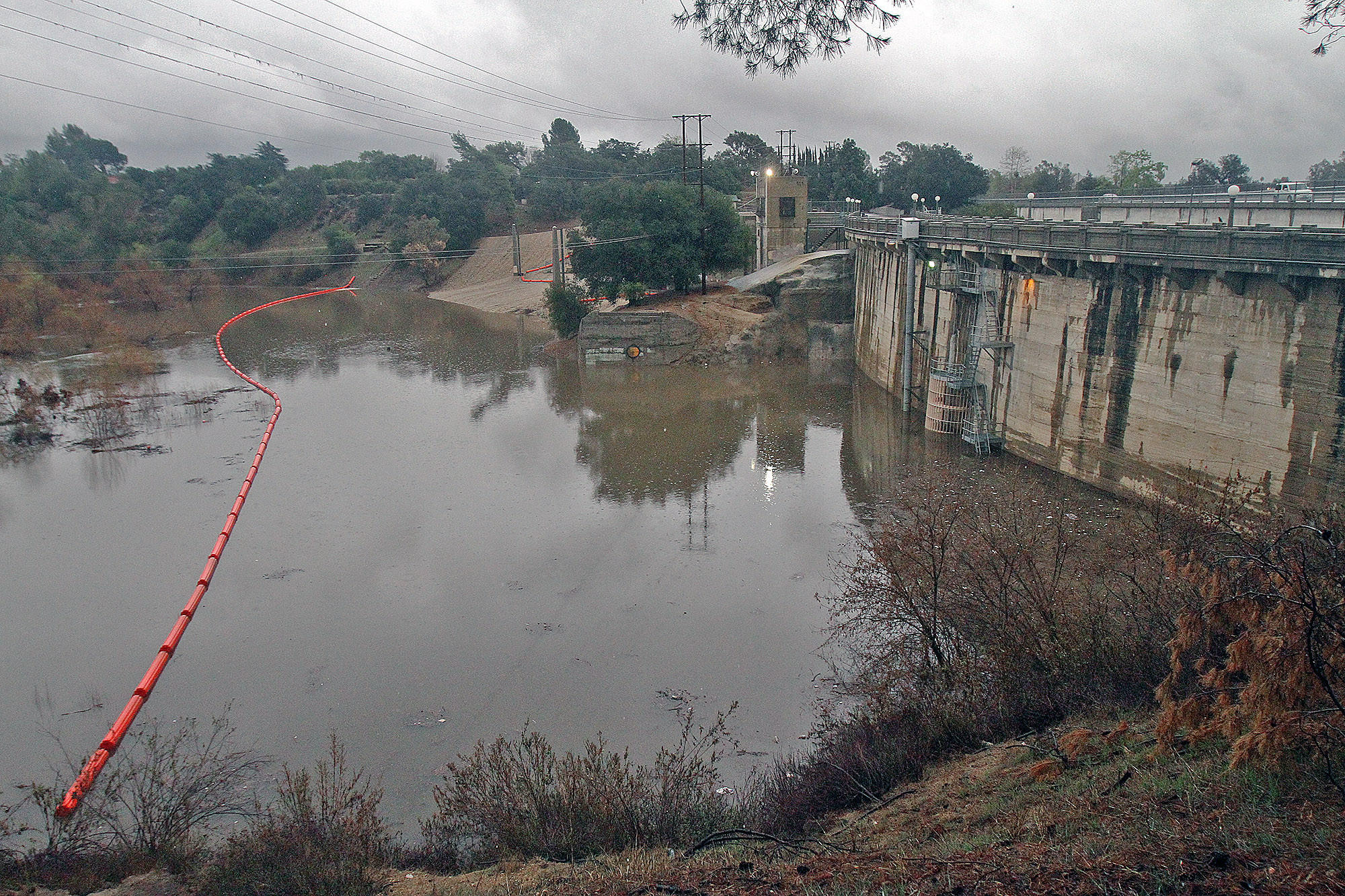 Devil's Gate Dam holds the rising Hahamongna watershed waters in check during the rain in Pasadena on Friday, Feb. 28, 2014.