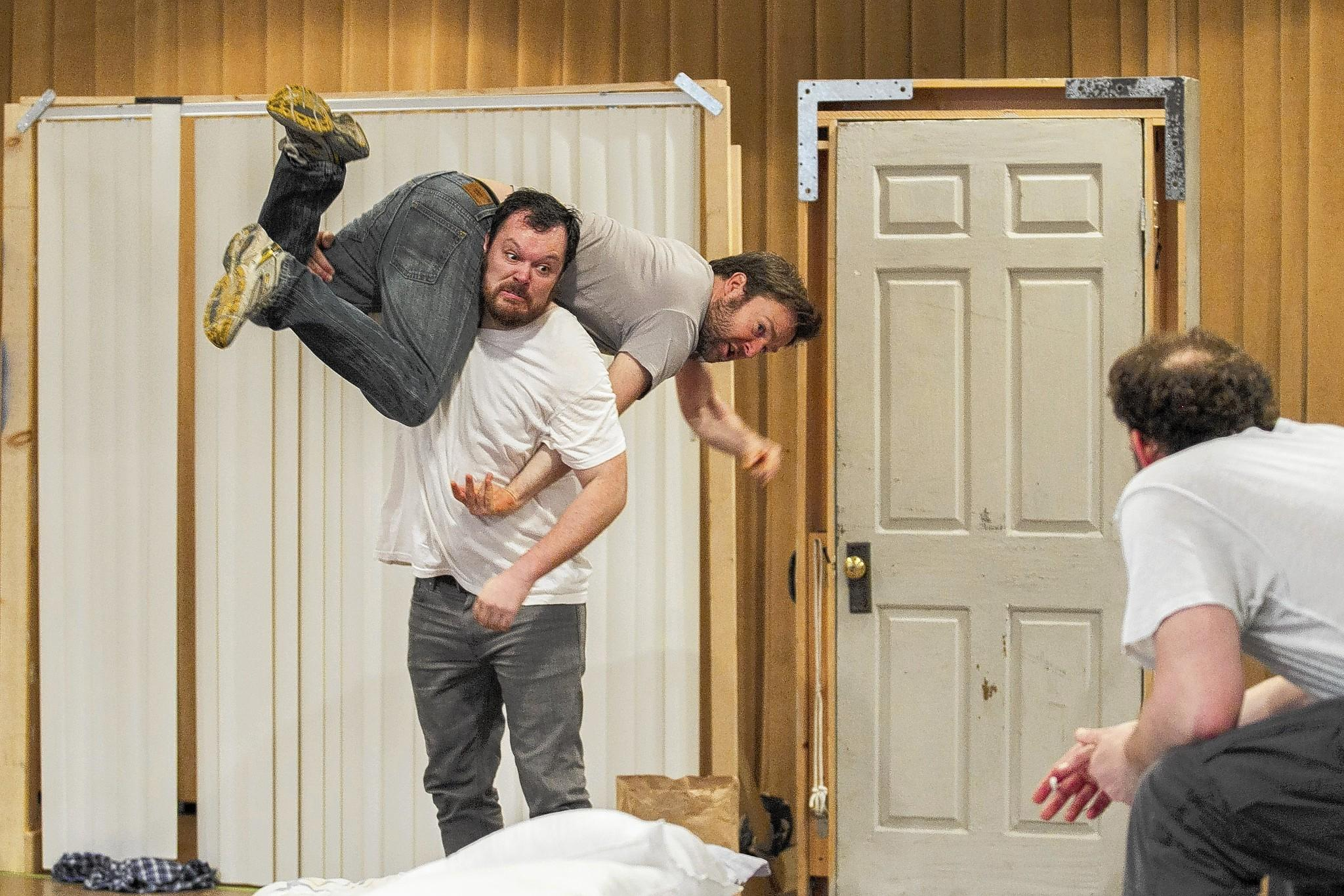 "Michael Gladis lifts Kevin Berntson as Tim Cummings, right, looks on during a rehearsal for Gregory S Moss' world premiere of ""Reunion"" at the South Coast Repertory."