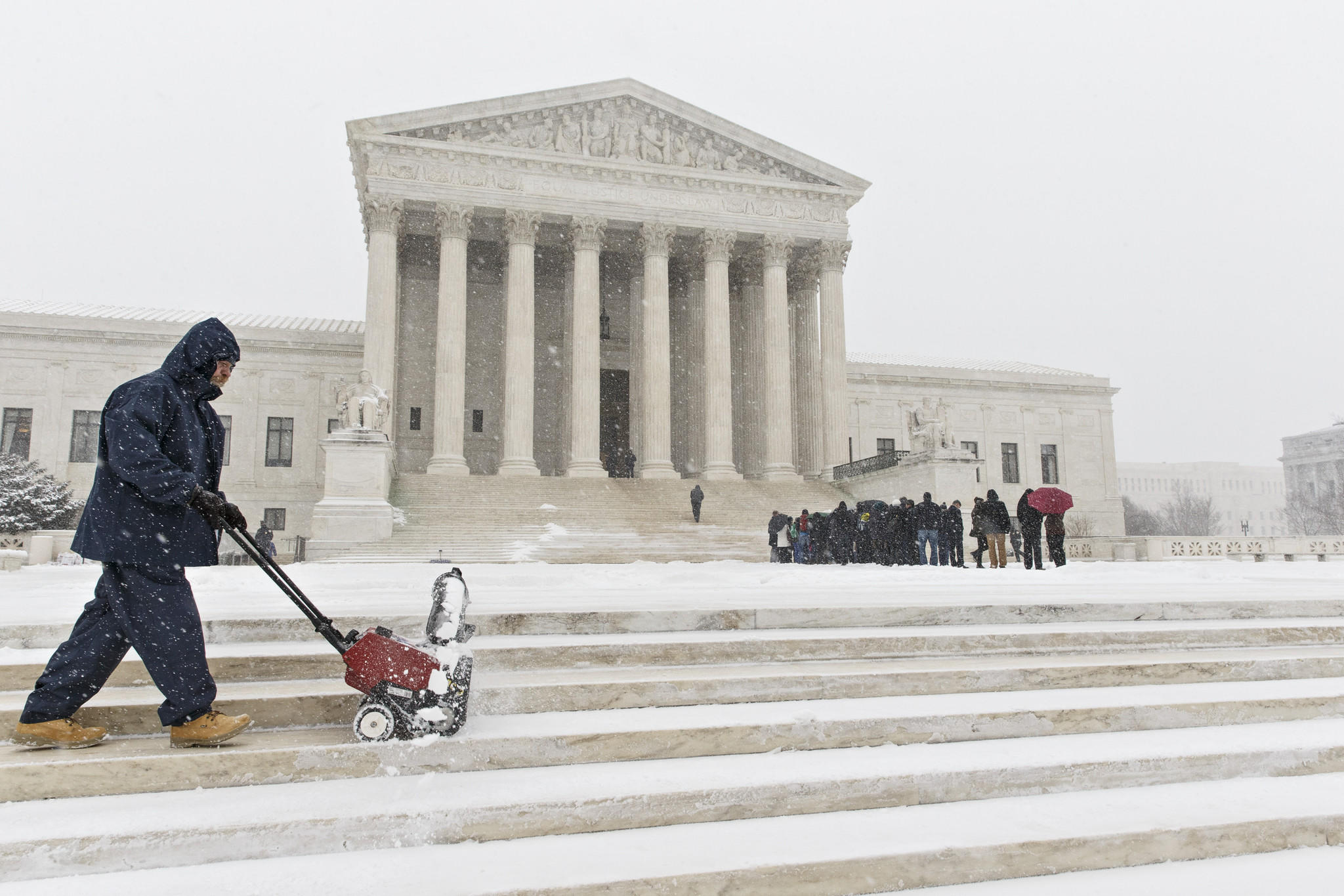 A worker clears snow from the plaza at the Supreme Court in Washington on Monday as those waiting to hear oral arguments line up.