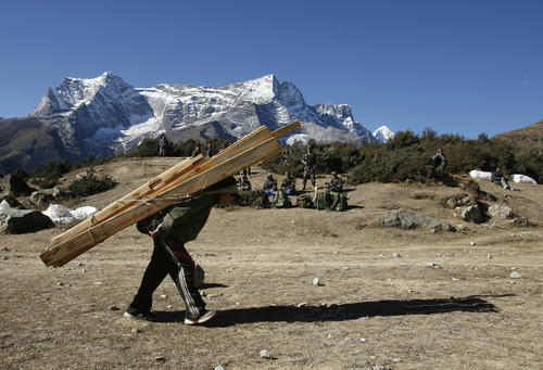 A porter carries timber from the Syangboche airstrip in Nepal December 3, 2009, near Mt. Everest.