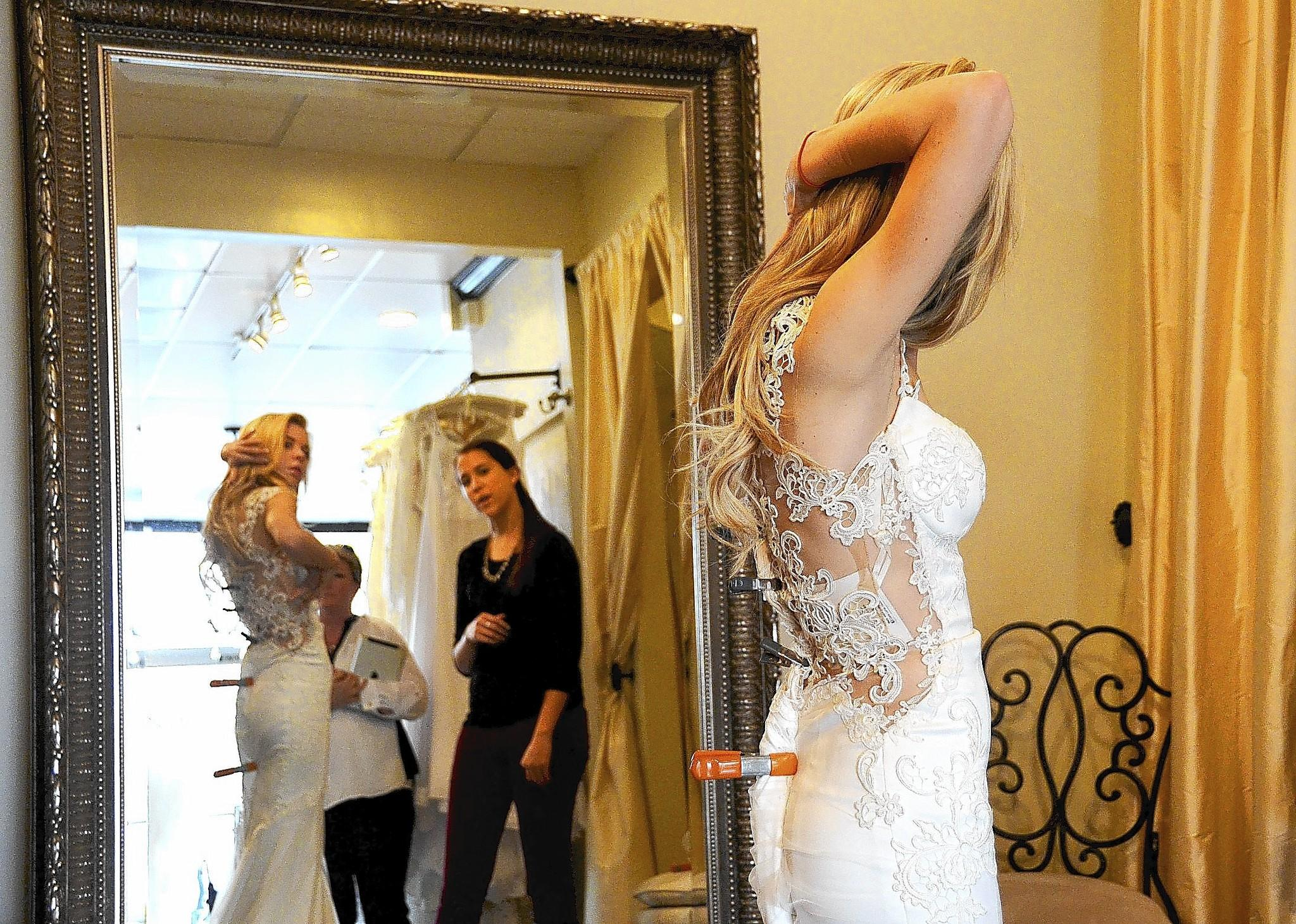 Bailey Buntain looks carefully at the lines on an elegant bridal gown in the fitting room while shopping at the The White Dress salon as part of the Corona Del Mar Bridal Walk on Sunday.