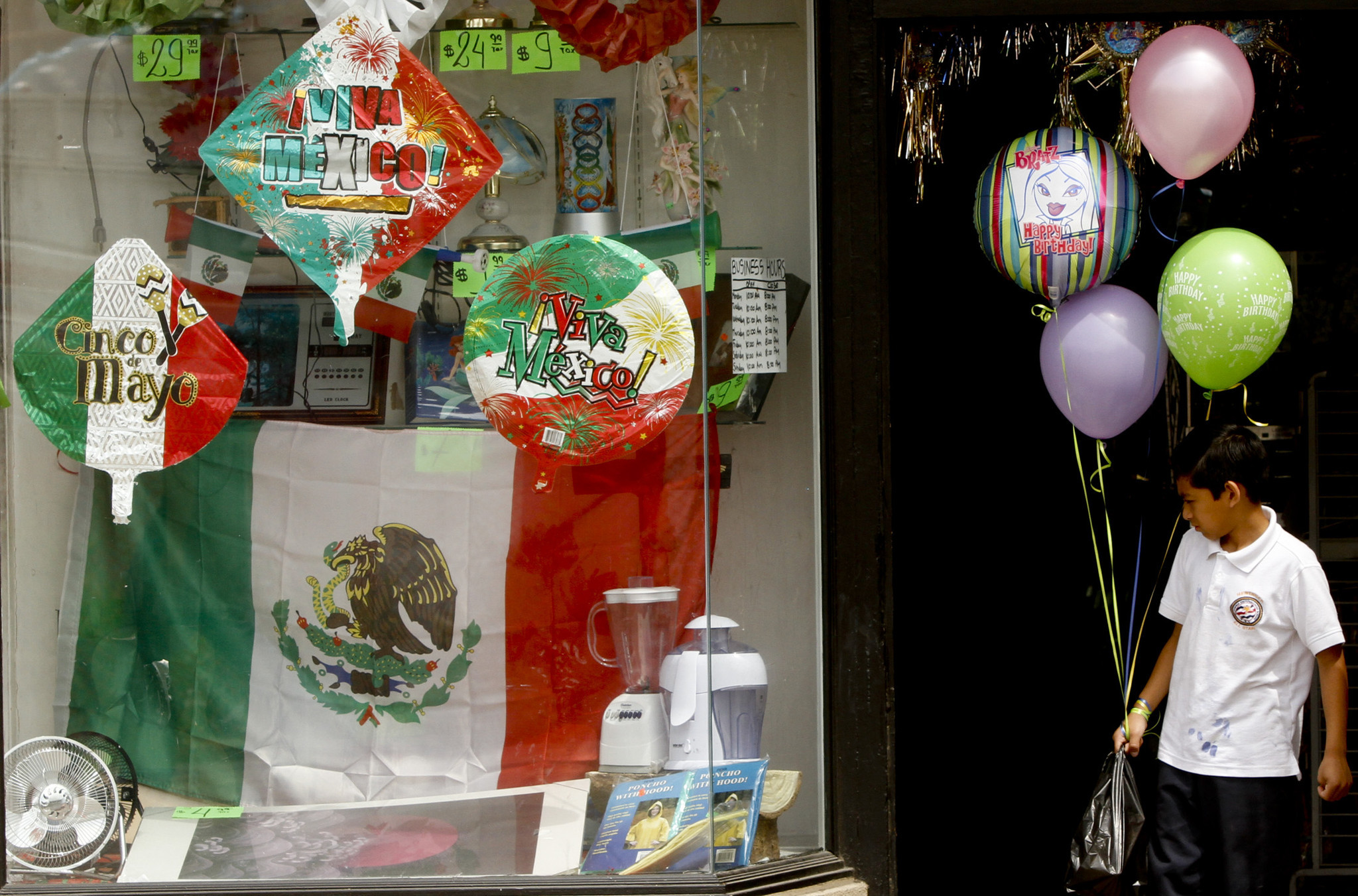 Alex Miramontes pauses in the doorway of the Double Discount store in downtown Santa Ana to look over the Cinco de Mayo display in the window.