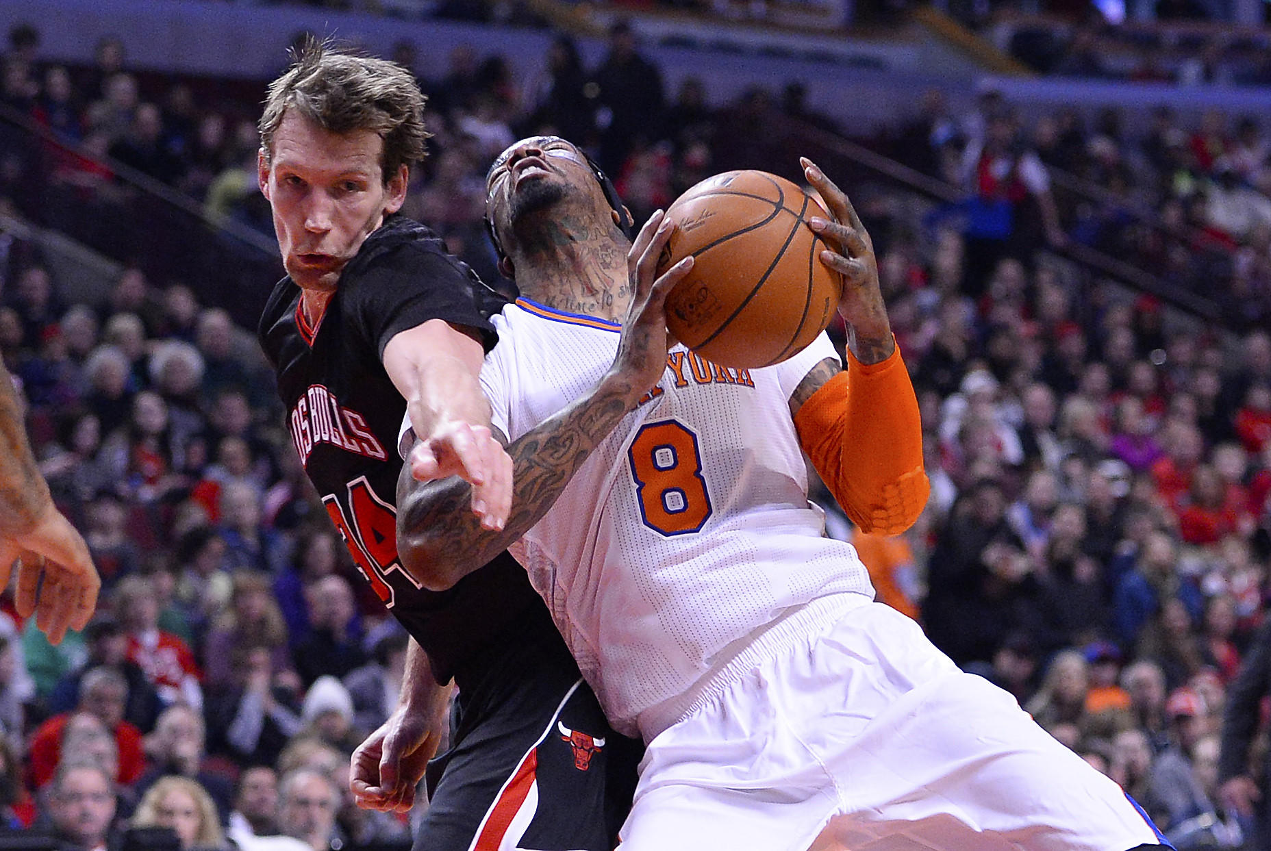 Mike Dunleavy fouls the Knicks' J.R. Smith during the first half at the United Center.