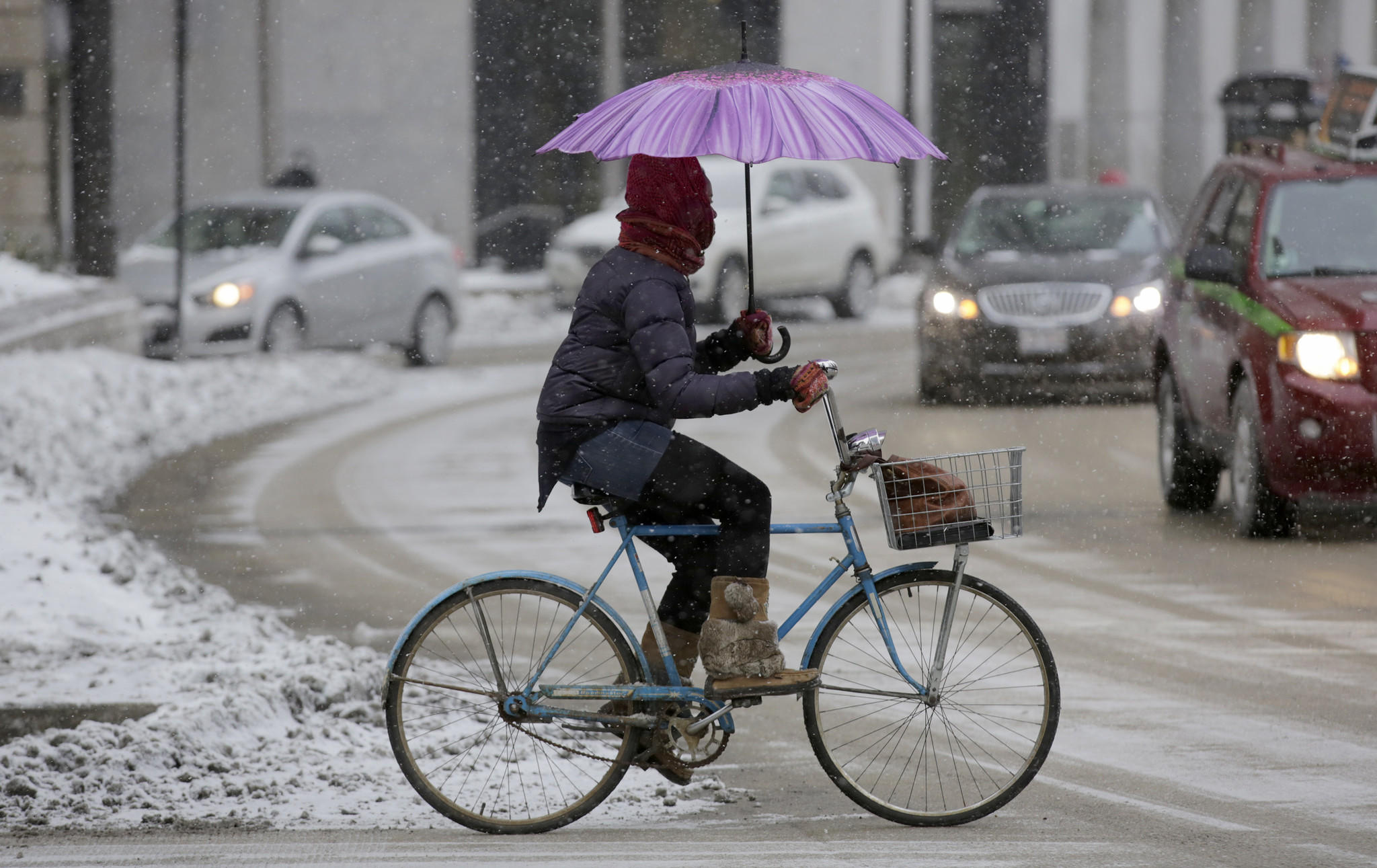 A cyclist fends off snow with an umbrella while riding north on Wabash Avenue at Wacker Drive Monday.