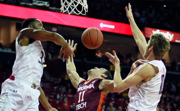 Virginia Tech's Devin Wilson is swarmed by Maryland's Dez Wells, left, and Jake Layman on Tuesday in College Park, Md.