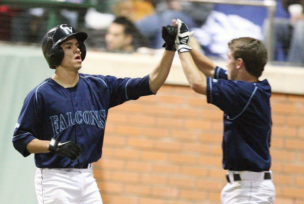 Crescenta Valley High's Nick Diaz gets a high five from Joe Torres after scoring the second run against La Cañada during a nonleague game at Stengel Field on Tuesday. (Roger Wilson/Staff Photographer)