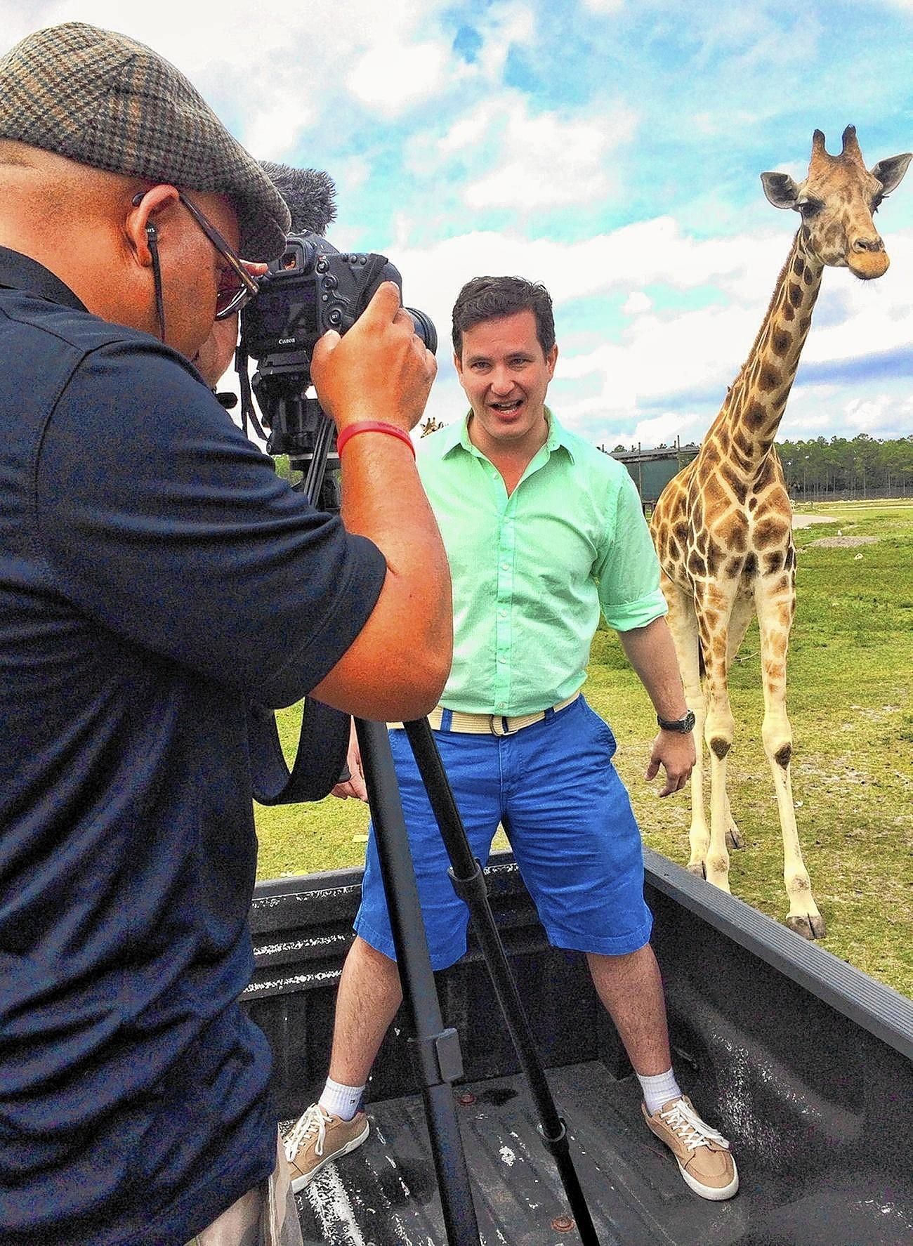 Brazilian host Renan Leahy, (right) gets up close to a giraffe at Lion Country Safari in Loxahatchee during filming for a new Palm Beach County travel video on Thursday, Feb. 27 with Brand USA videographer Amon Focus.
