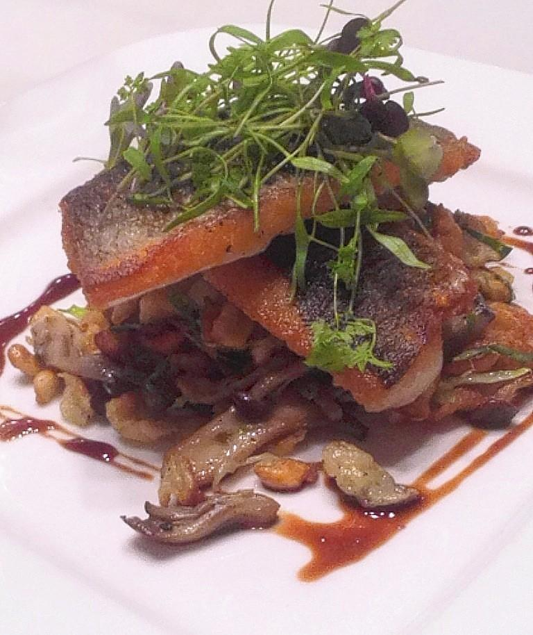 Two crisp filets of pan-roasted Mediterranean sea bass, rests on a mound of fried spaetzle with mushrooms and Brussels sprouts.