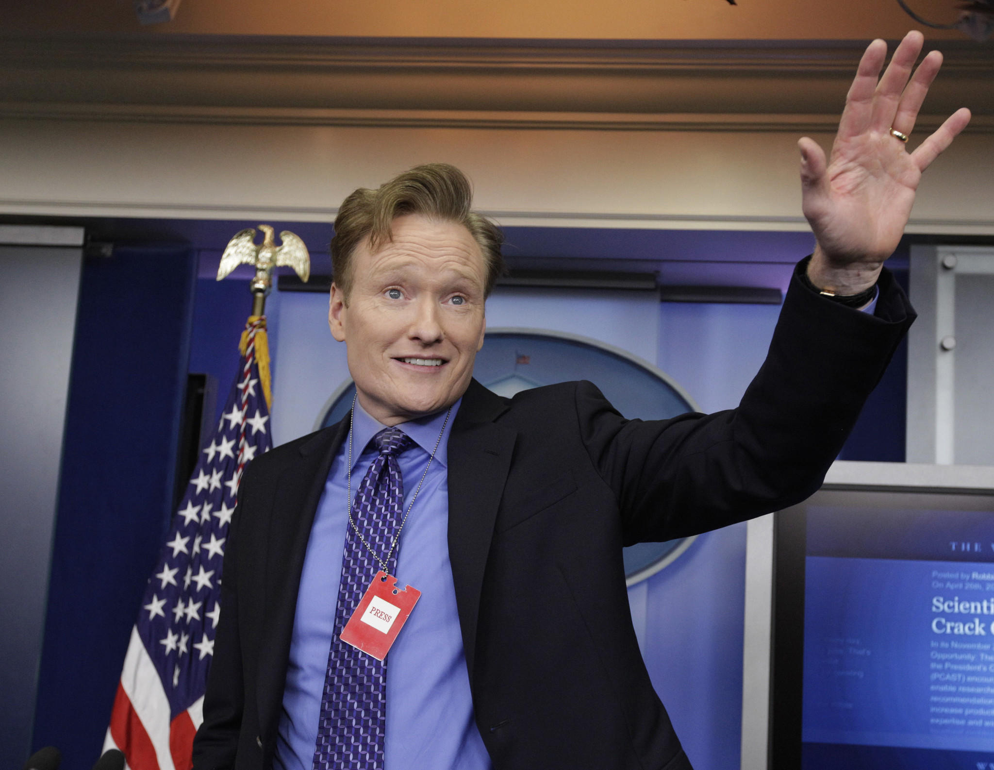 Television host Conan O'Brien poses for photographs while on a tour of the media work area at the White House.