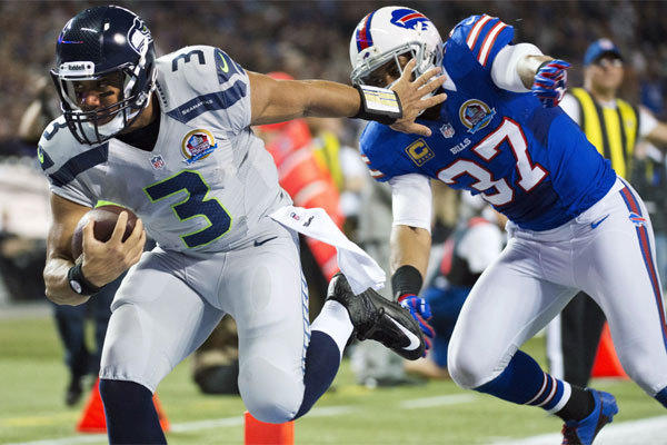 Seattle quarterback Russell Wilson runs the ball into the end zone past Buffalo's George Wilson during a 2012 game in Toronto.