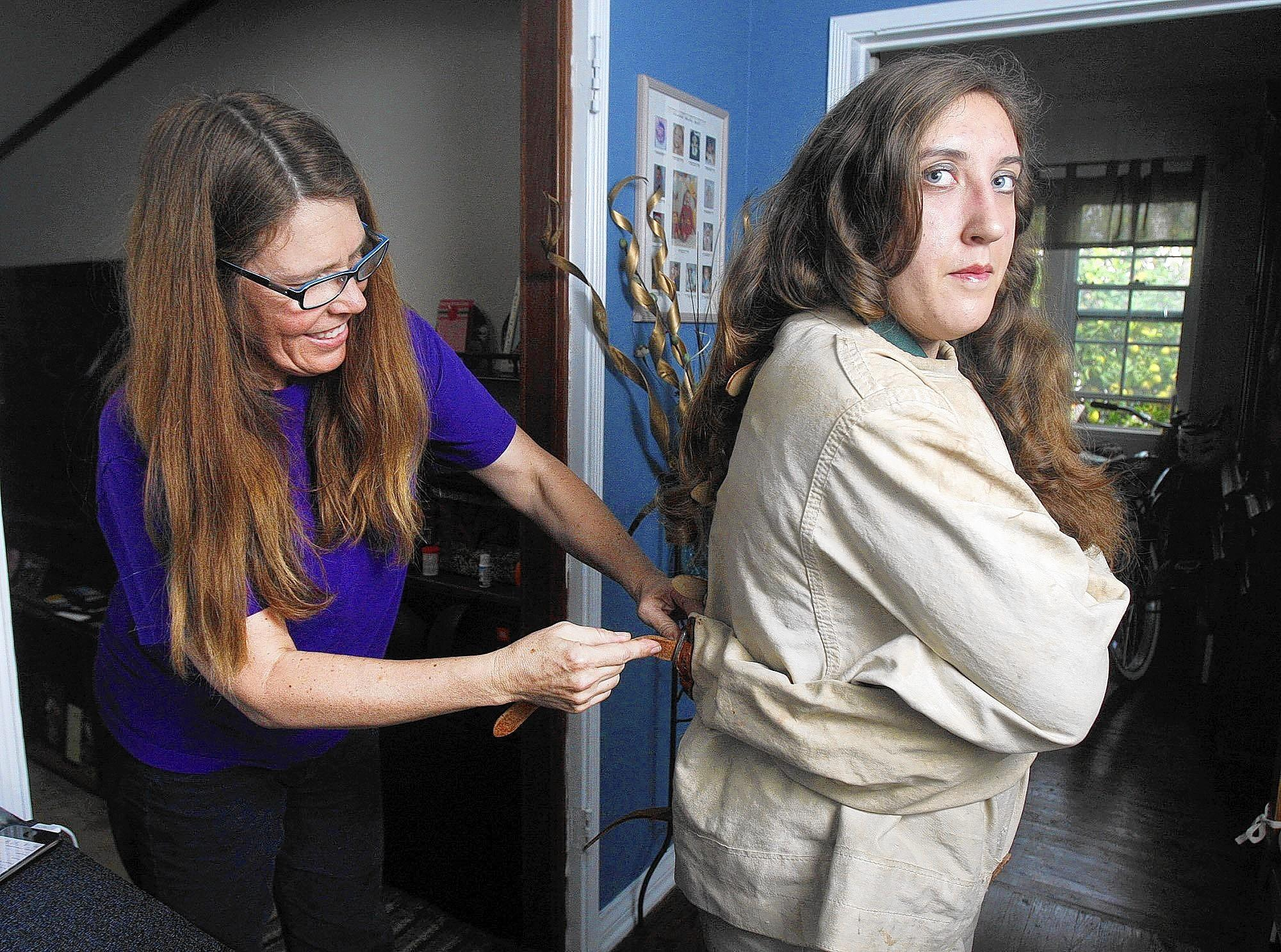 London Ruff, 17, of Burbank,is secured into a straight jacket by her mom, Wendy, in her home on Monday, March 3, 2014. Professionals are mentoring Ruff in the Magic Castle program. She will perform at Providence High School to raise money for the school. One of her magic specialties is escaping from a straight jacket.
