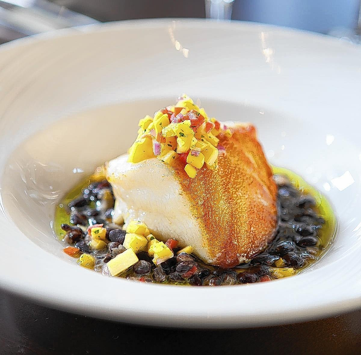 The fresh catch changes daily at deep blu seafood grille. This sea bass is served on a saute of black beans topped with mango relish.
