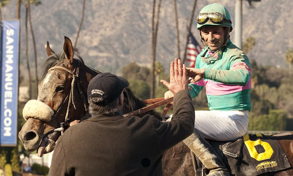 Jockey Aaron Gryder is congratulated by trainer John Shirreffs after riding Blingo to victory in the Grade II San Antonio Stakes at Santa Anita on Feb. 8. While his globetrotting days may be over, Gryder continues to build upon his reputation as a talented jockey.