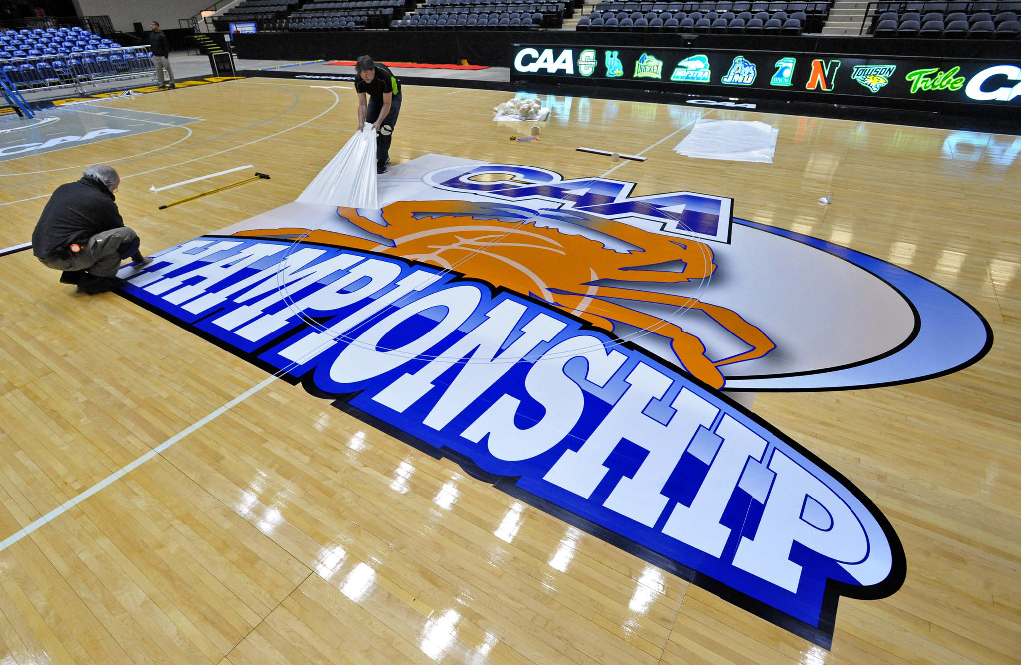 Dick Hageman (left) and Jeff Knab of Art At Work install the CAA logo and other decals on the court at Baltimore Arena on Wednesday.