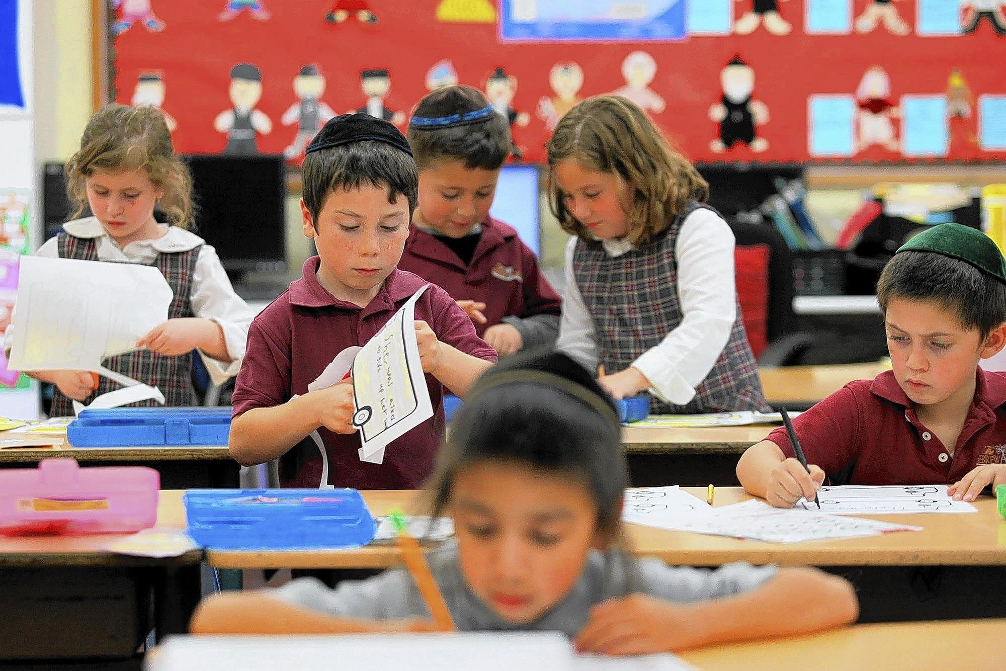 First-graders work on an activity during Susan Choi's General Studies class at the Hebrew Academy in Huntington Beach.