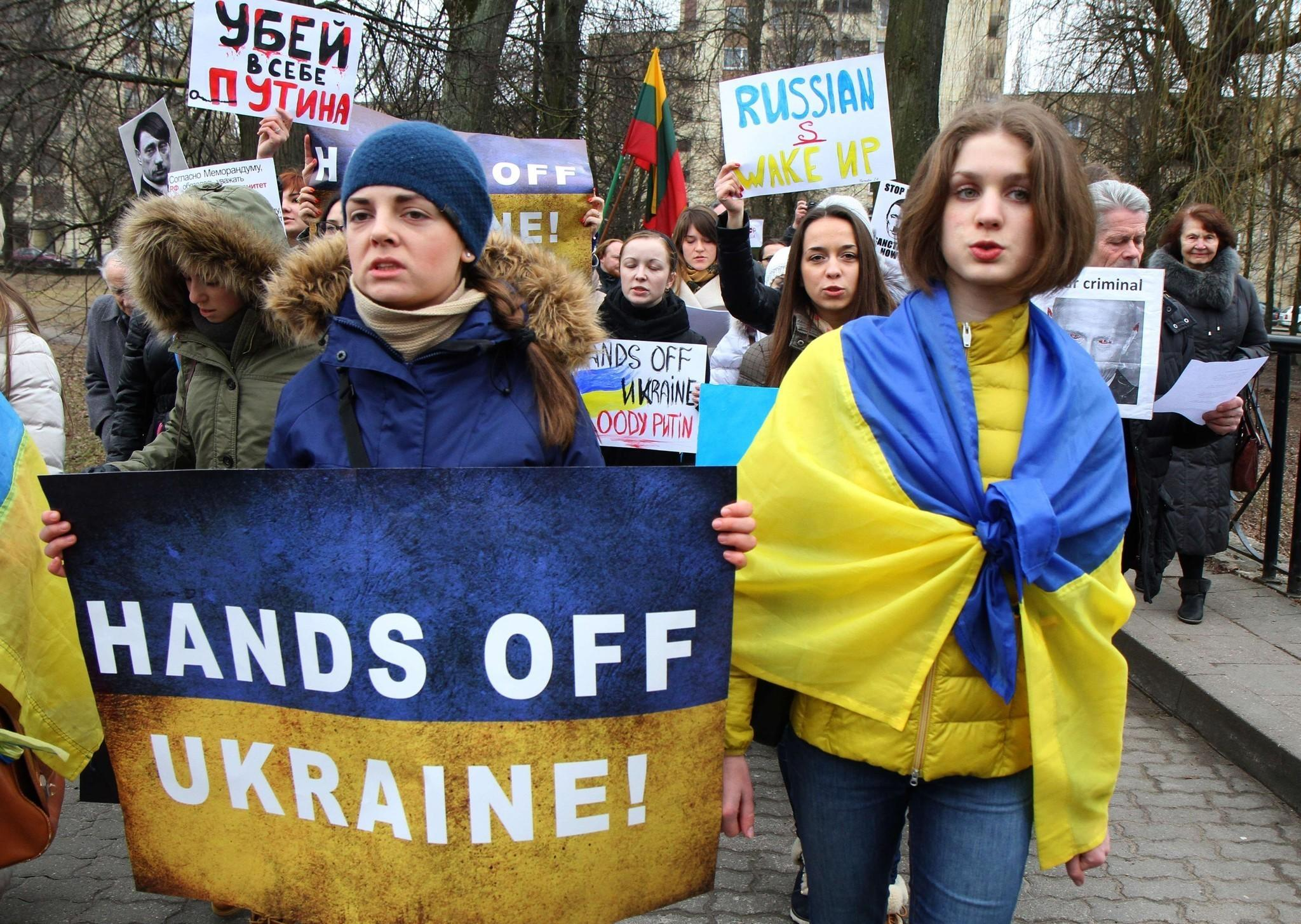 "Demonstrators wear the Ukrainian flag and hold posters reading ""Hands off Ukraine"" during a protest of Russia's intervention in Ukraine at the Russian Embassy in Vilnius, Lithuania, on March 3, 2014."
