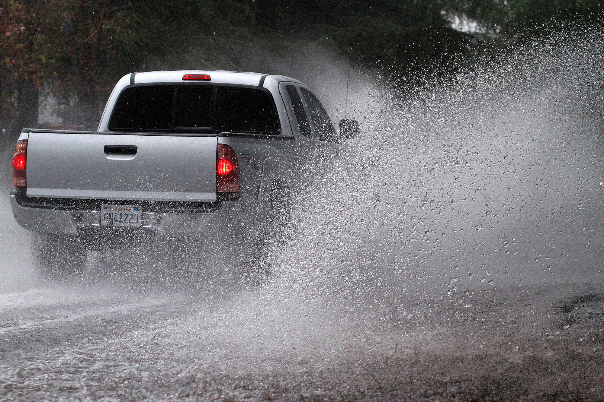 Cars and trucks on Ocean View Boulevard in La Cañada Flintridge, near the Glendale area, drive through a strong current of water running down the middle of the road on Friday, Feb. 28, 2014. Periodic heavy rain continued through the weekend.