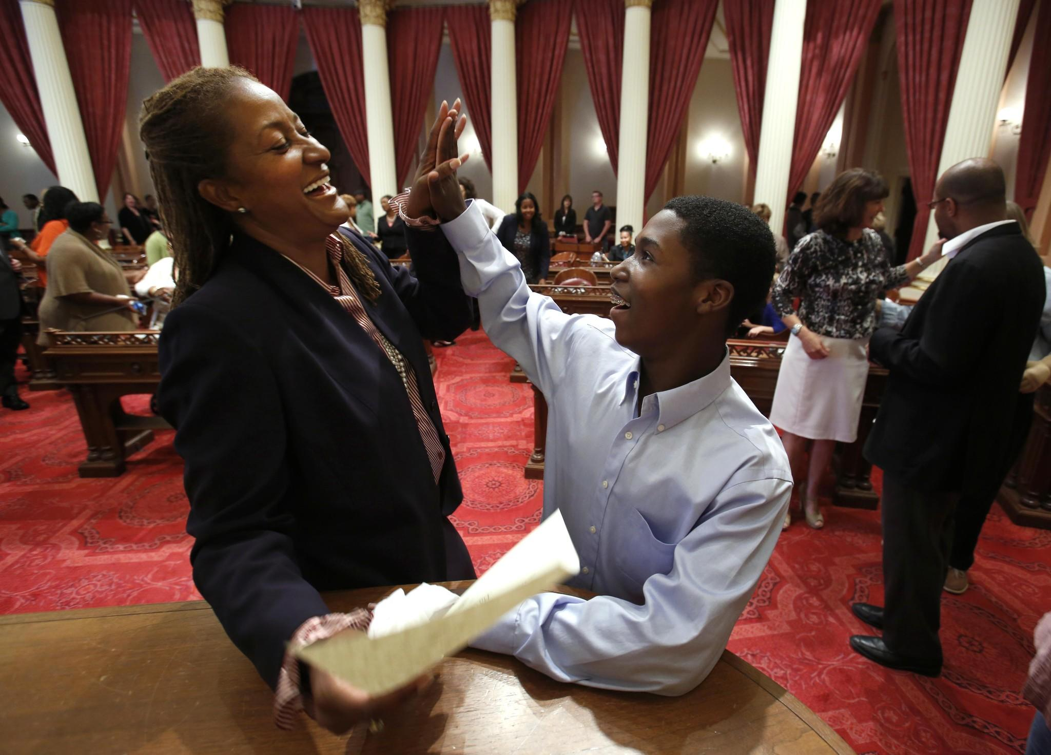 Sen. Holly Mitchell (D-Los Angeles)is the only African American in the state Senate after Sen. Roderick Wright took a leave of absence. Above, Mitchell gets a high-five from her son, Ryan, 13, after signing her oath of office at the Capitol last fall.