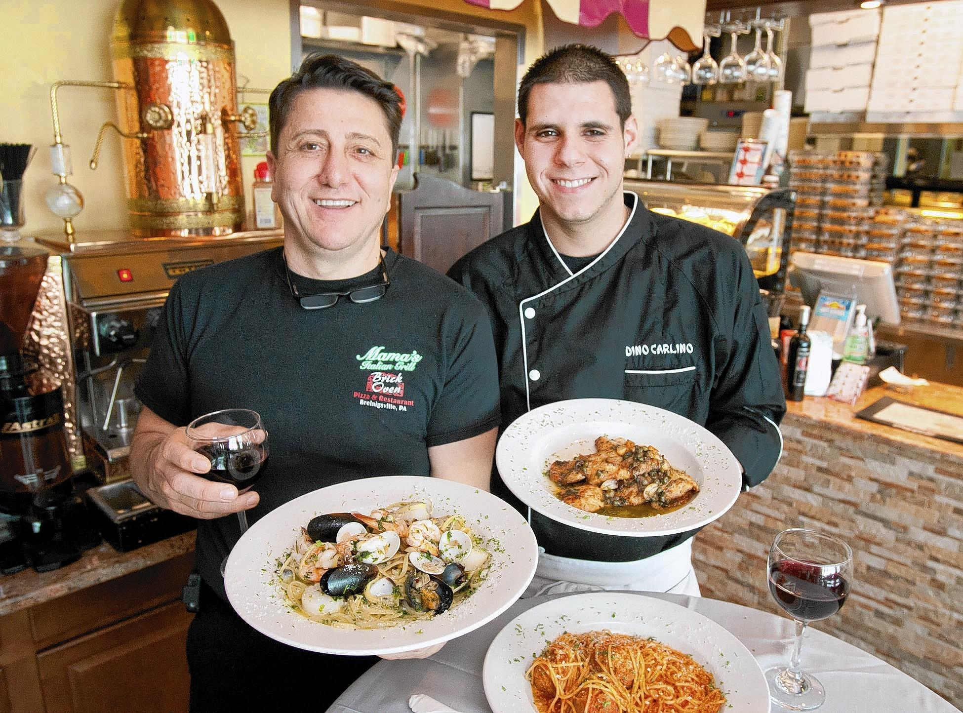 Mama's Italian Grill owner Giuseppe DiFiore (left) and chef Dino Carlino hold plates of the Seafood Combination and Chicken Piccata at Mama's Italian Grill in Upper Macungie Township.