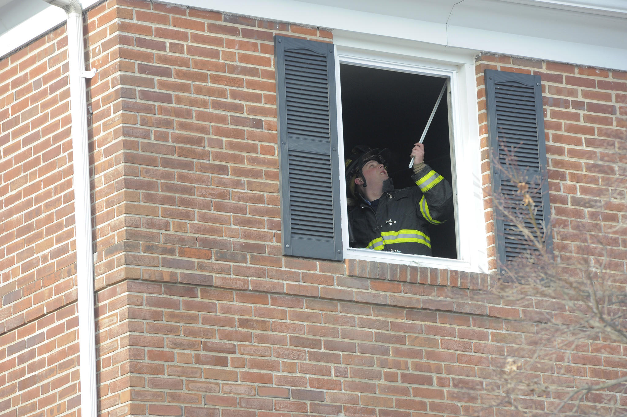 A Baltimore City firefighter removes a curtain rod before covering an open window with plastic sheeting.