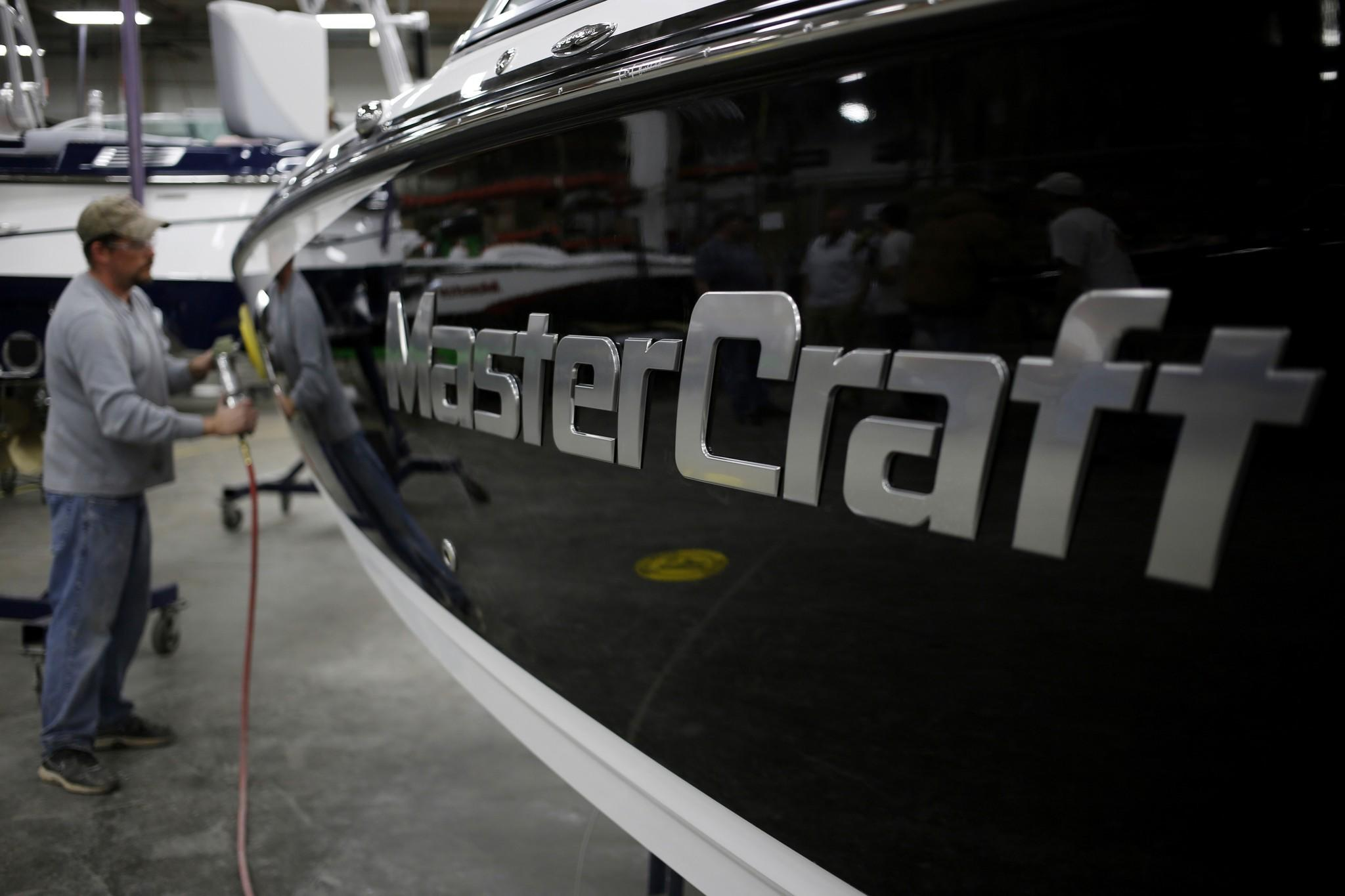 Kevin Russell buffs the finish on a speedboat on the assembly line at the Mastercraft factory in Vonore, Tenn.